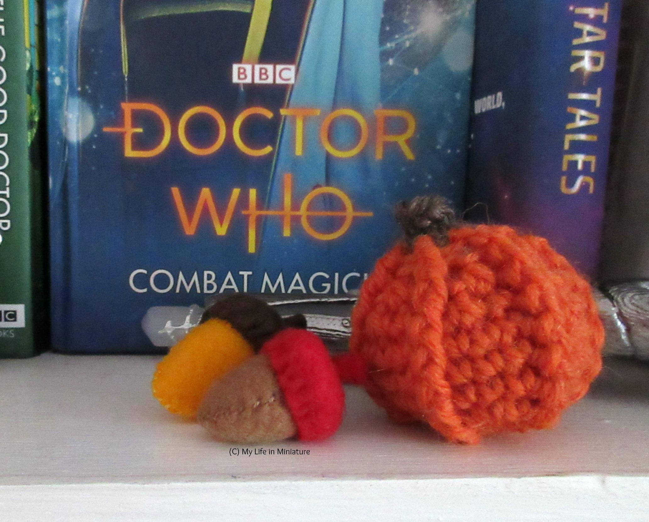 Two felt acorns sit on a bookshelf, next to a crocheted orange pumpkin.