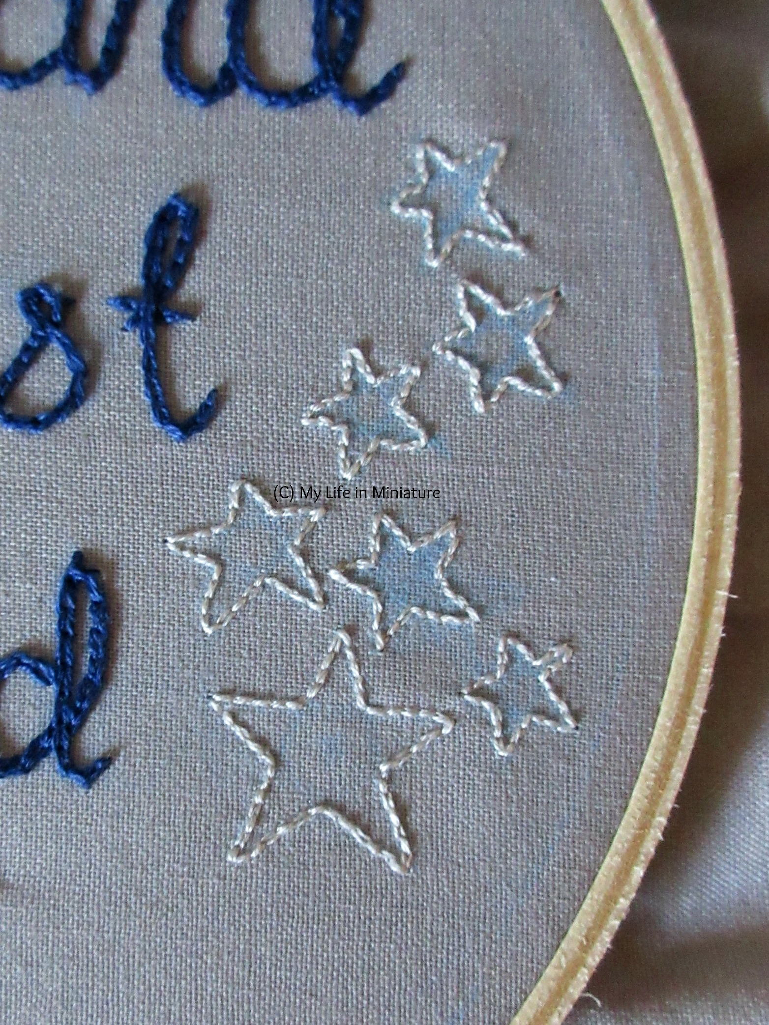 The right hand side of the grey-fabric-filled embroidery hoop is visible. Seven stars are outlined in backstitch in silver, scattered in a loosely vertical manner.
