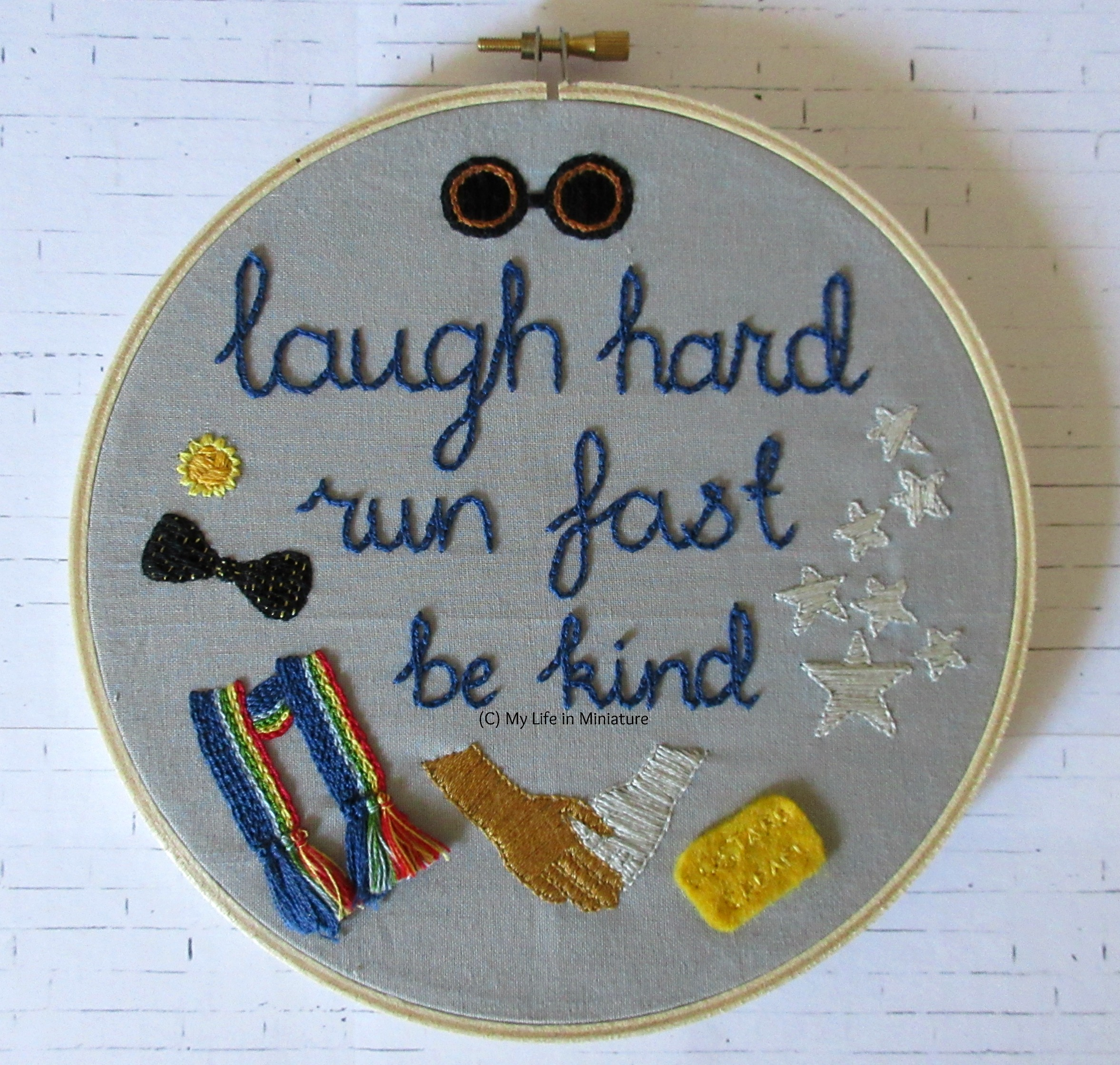 The embroidery hoop, filled with grey fabric, sits on a white brick background. The phrase 'laugh hard; run fast; be kind' is embroidered in navy blue in the middle. Around it are various symbols of the Thirteenth Doctor, including a daffodil flower, a rainbow-striped scarf, and a custard cream biscuit.