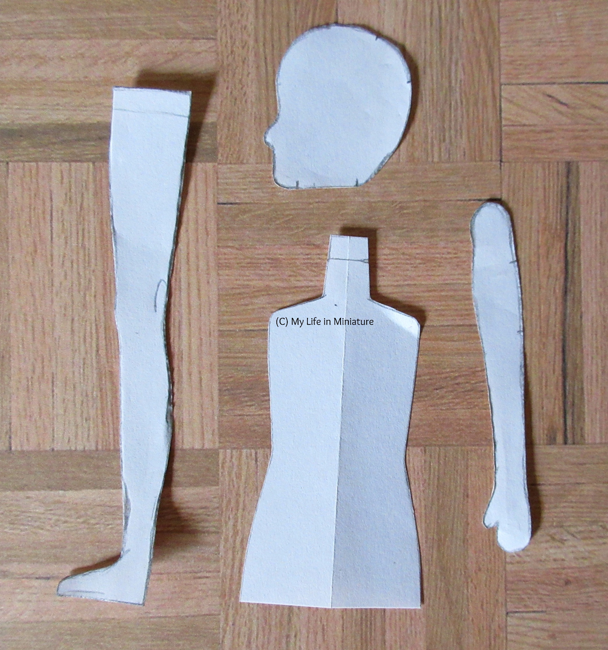 Pattern pieces for a miniature head, leg, torso and arm lie on a wood parquet background.