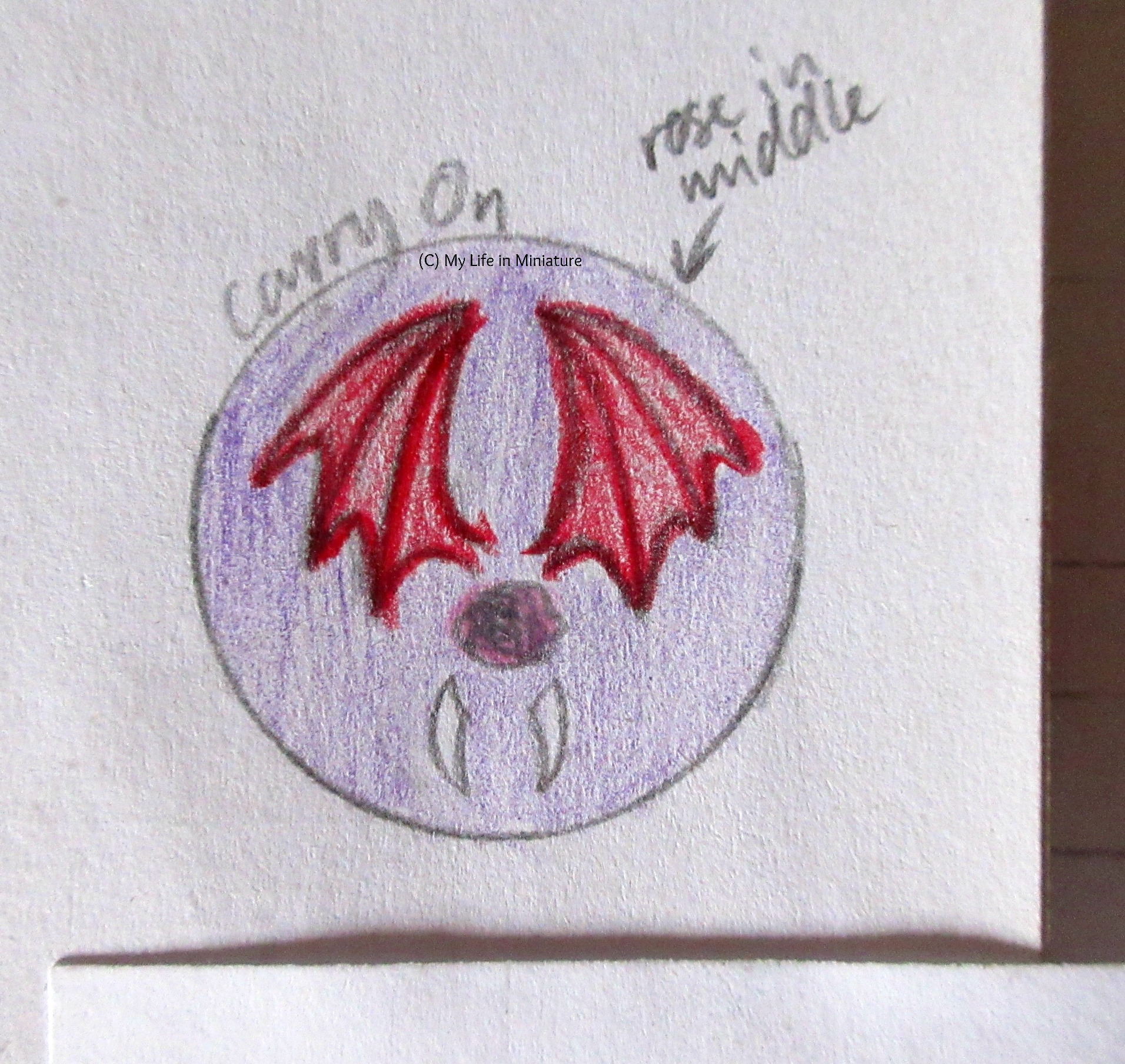 A sketch from a sketchbook shows a badge design inspired by 'Carry On' by Rainbow Rowell. A pink rose is in the centre, with red dragon wings above and two vampire teeth below. There is a purple background.