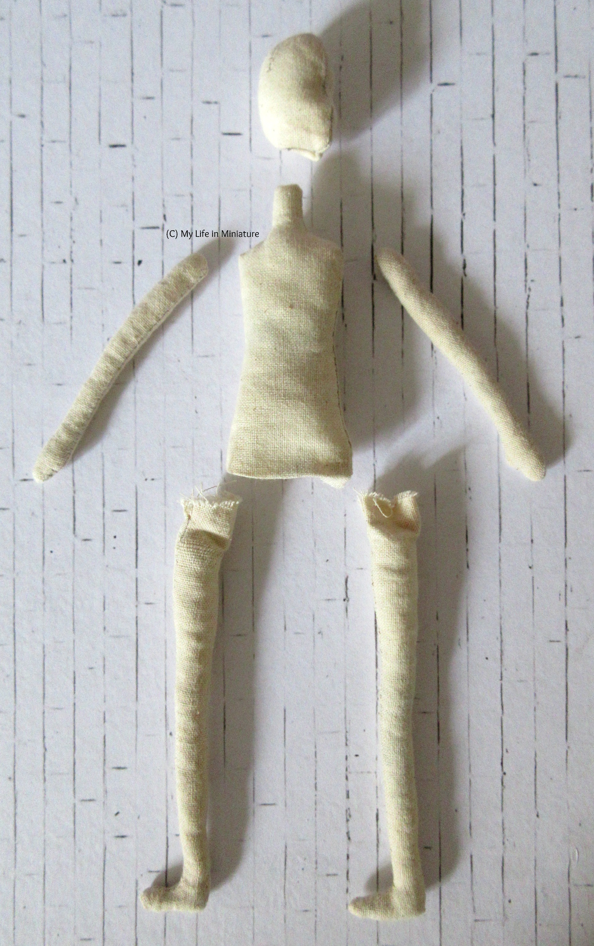 All the completed parts to a muslin doll are laid out on a white brick background, roughly in position to make a doll.