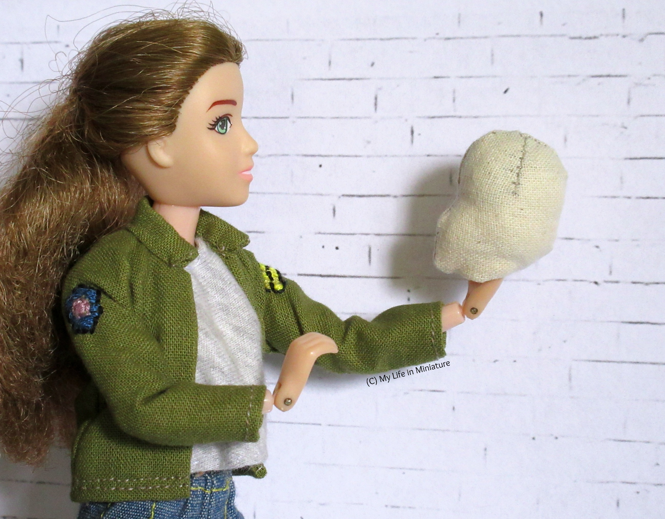 Sarah holds the stuffed head of the muslin doll in one hand. She holds it out away from herself, with the head looking back at her. She looks at the head. The whole pose is reminiscent of Hamlet.