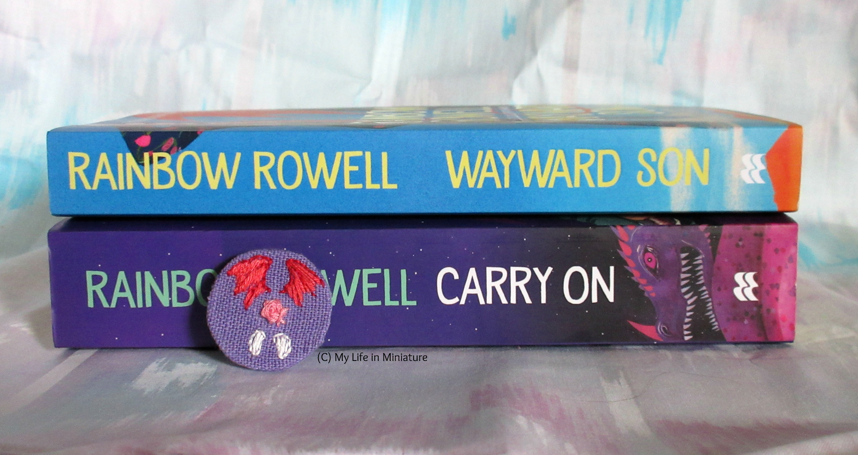 'Carry On' and 'Wayward Son' by Rainbow Rowell sit stacked on each other, spines facing the camera. The badge leans up against the spine of 'Carry On'.