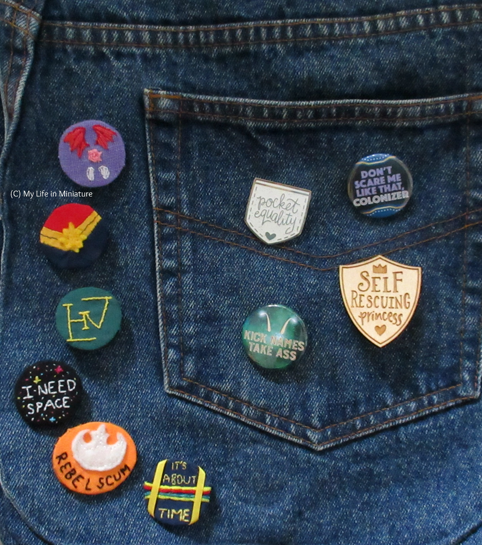 The badge is pinned onto a denim bag, alongside a variety of other badges and pins - both handmade and purchased.