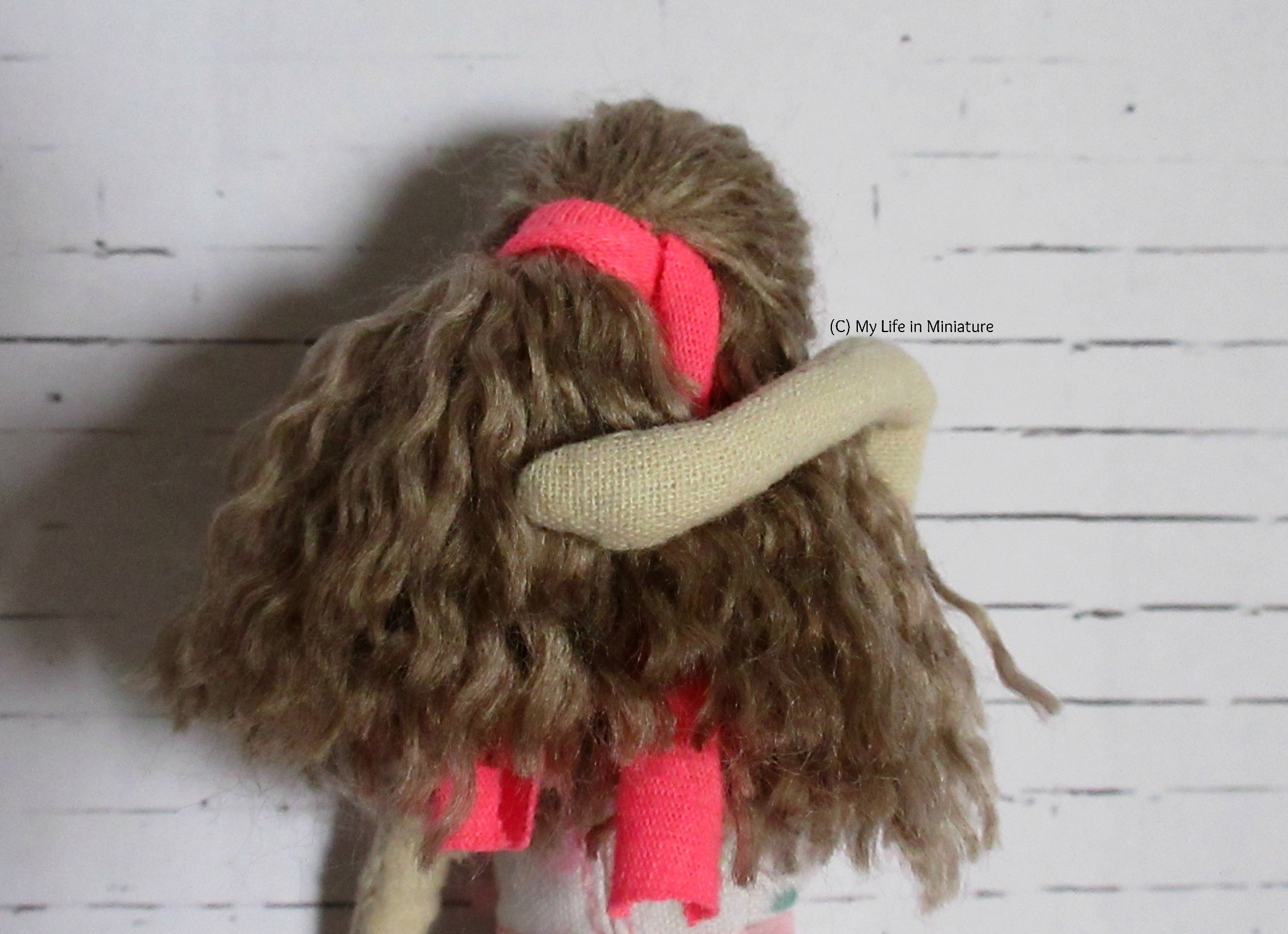The muslin handmade doll stands against a white brick background, back to the camera. One hand is smoothing down her hair, in which is visible a strip of pink jersey fabric tying back half the hair.