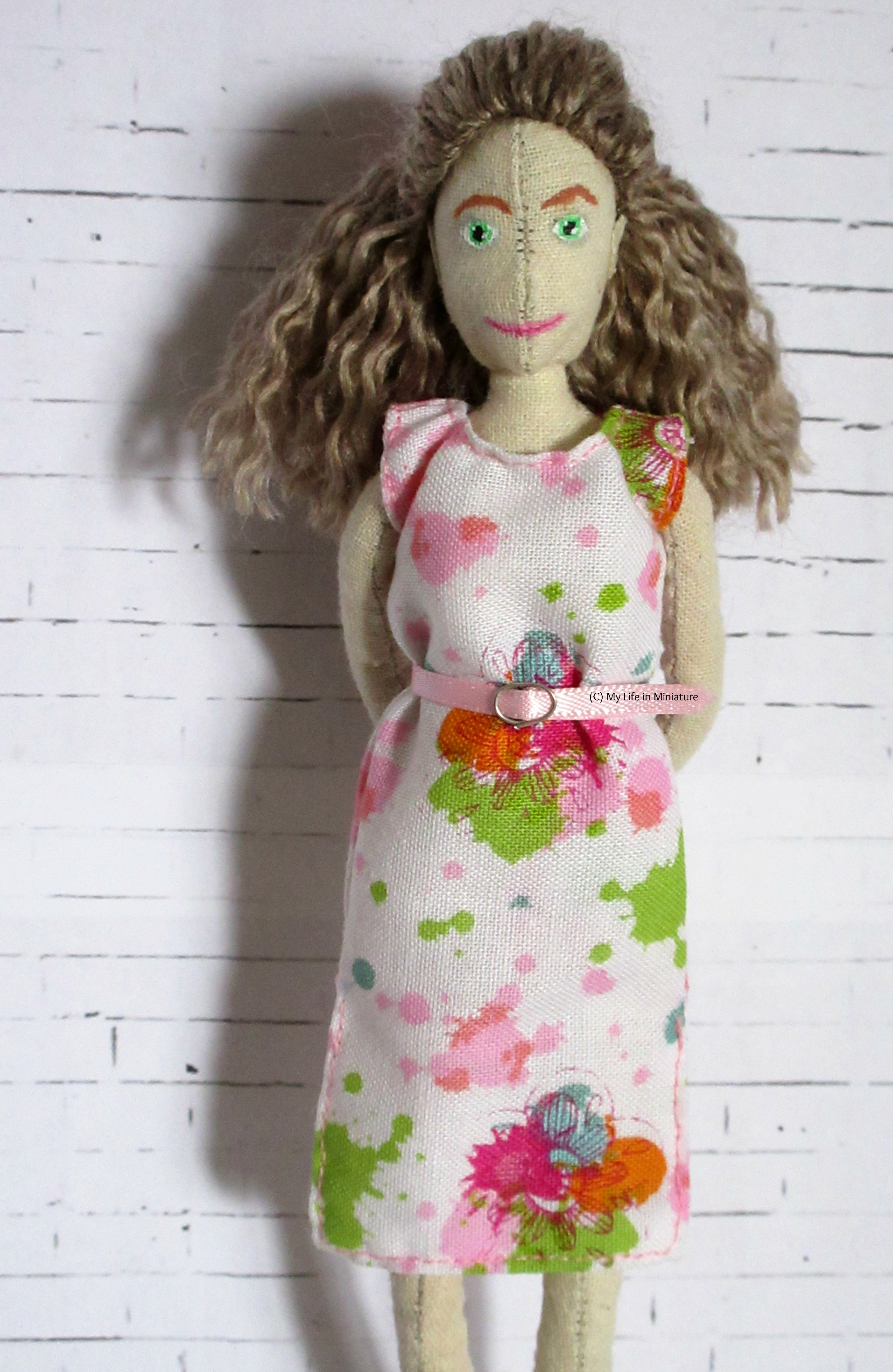 The muslin doll, Lola, wears a white, pink, and green floral knee-length dress with a pink belt. Her hands are behind her back and she looks at the camera.