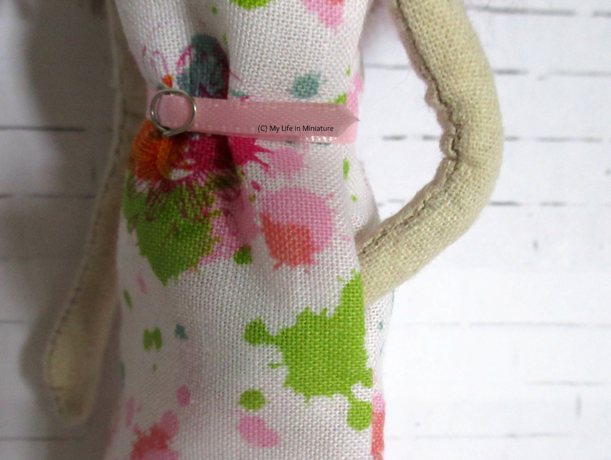 Close-up of the side of Lola's dress. Her hand is in the side-seam pocket in the dress, and the belt is visible.