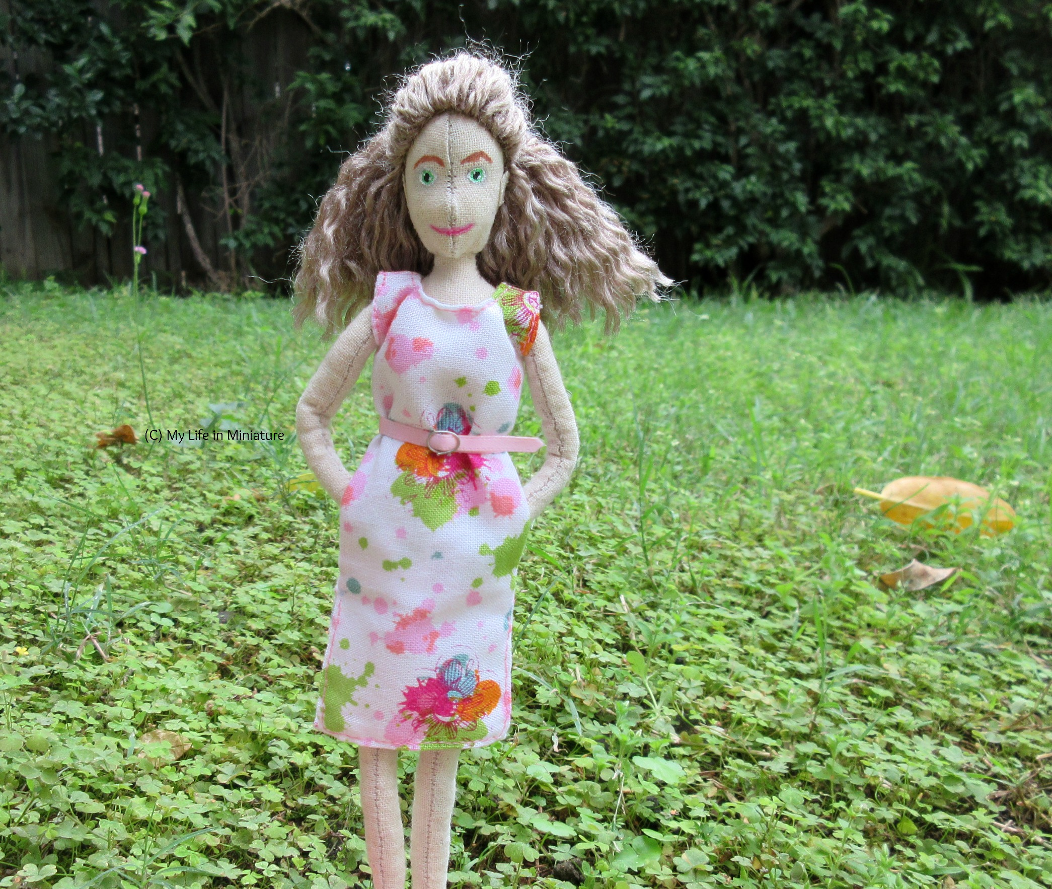 Lola stands on grass, with a hedge behind her. She wears the dress, with hands in pockets. She looks at the camera.