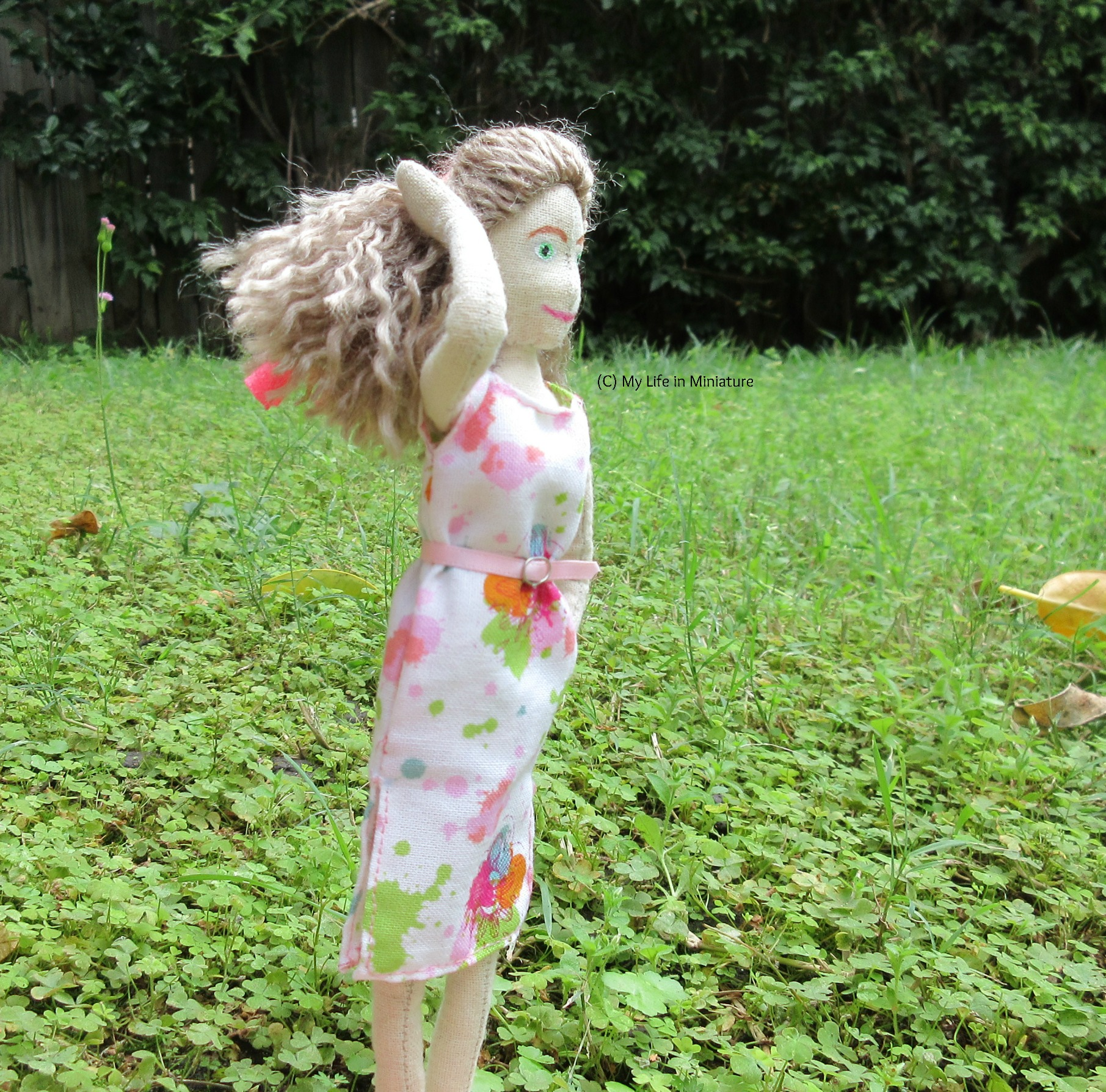 Lola stands on grass, with a hedge behind her. She has one hand on her hair and the other in her pocket, and she looks to the right.