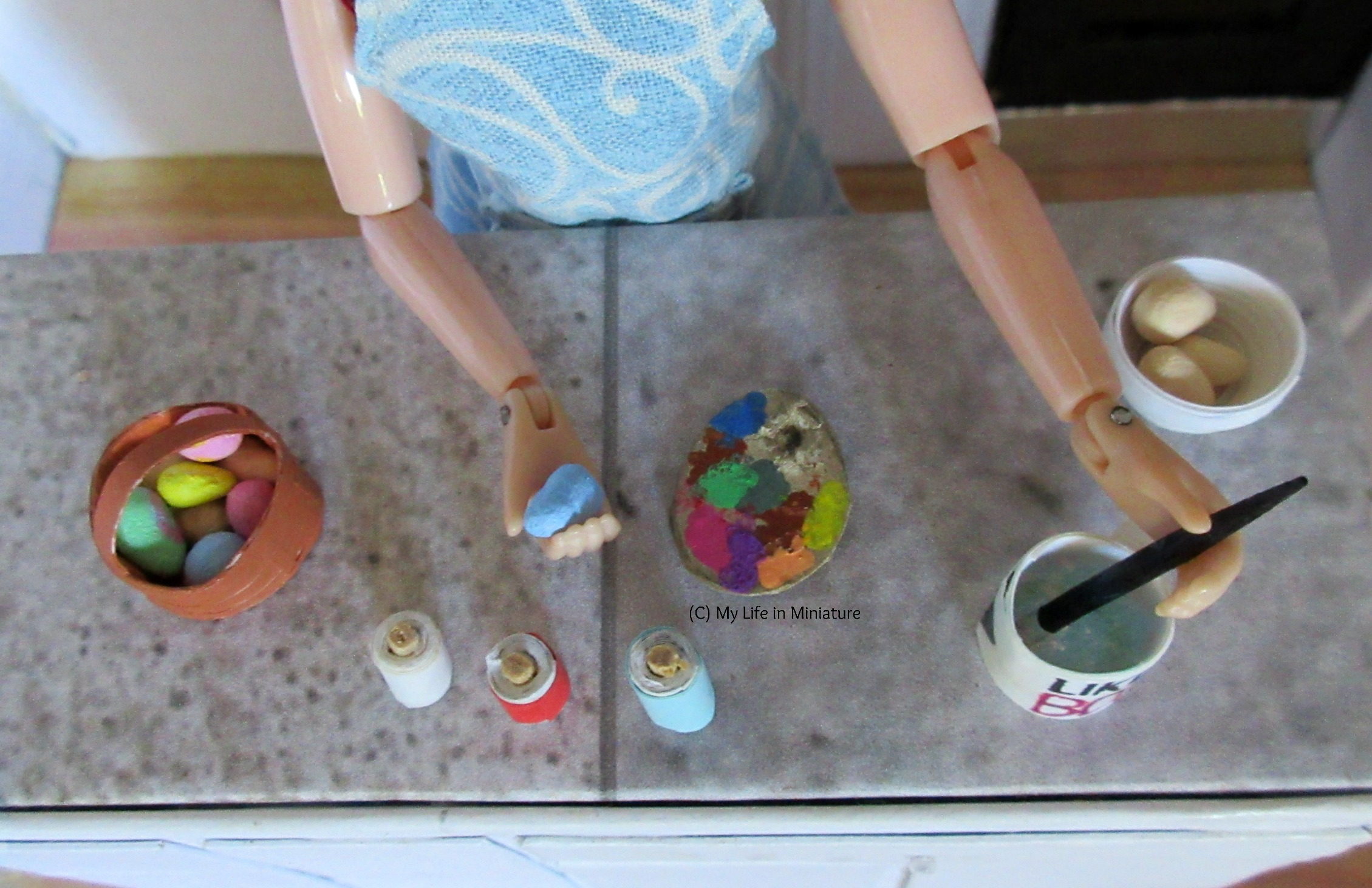 Shot from above of the previous scene. One hand holds a blue egg, and the other holds a paintbrush in a cup of water.