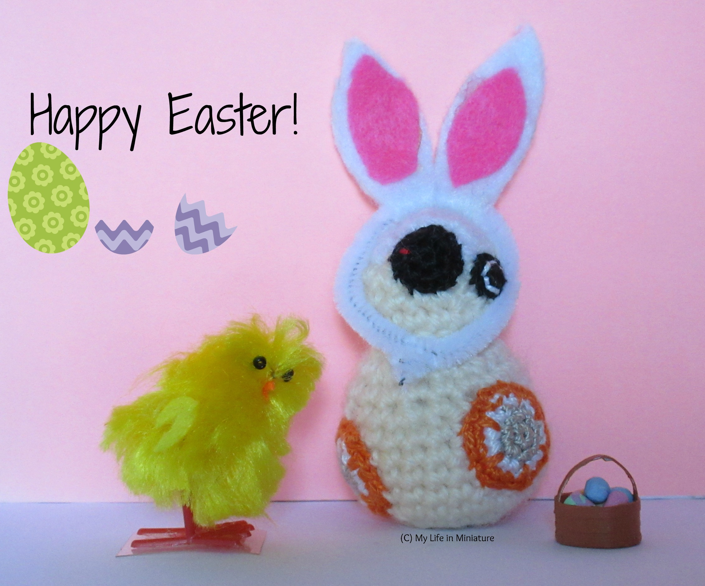 BB-8 sits in front of a pink background, wearing bunny ears. A plastic chick is beside him, as well as a basket of painted eggs. The words 'Happy Easter!' are to the top left, surrounded by egg graphics.