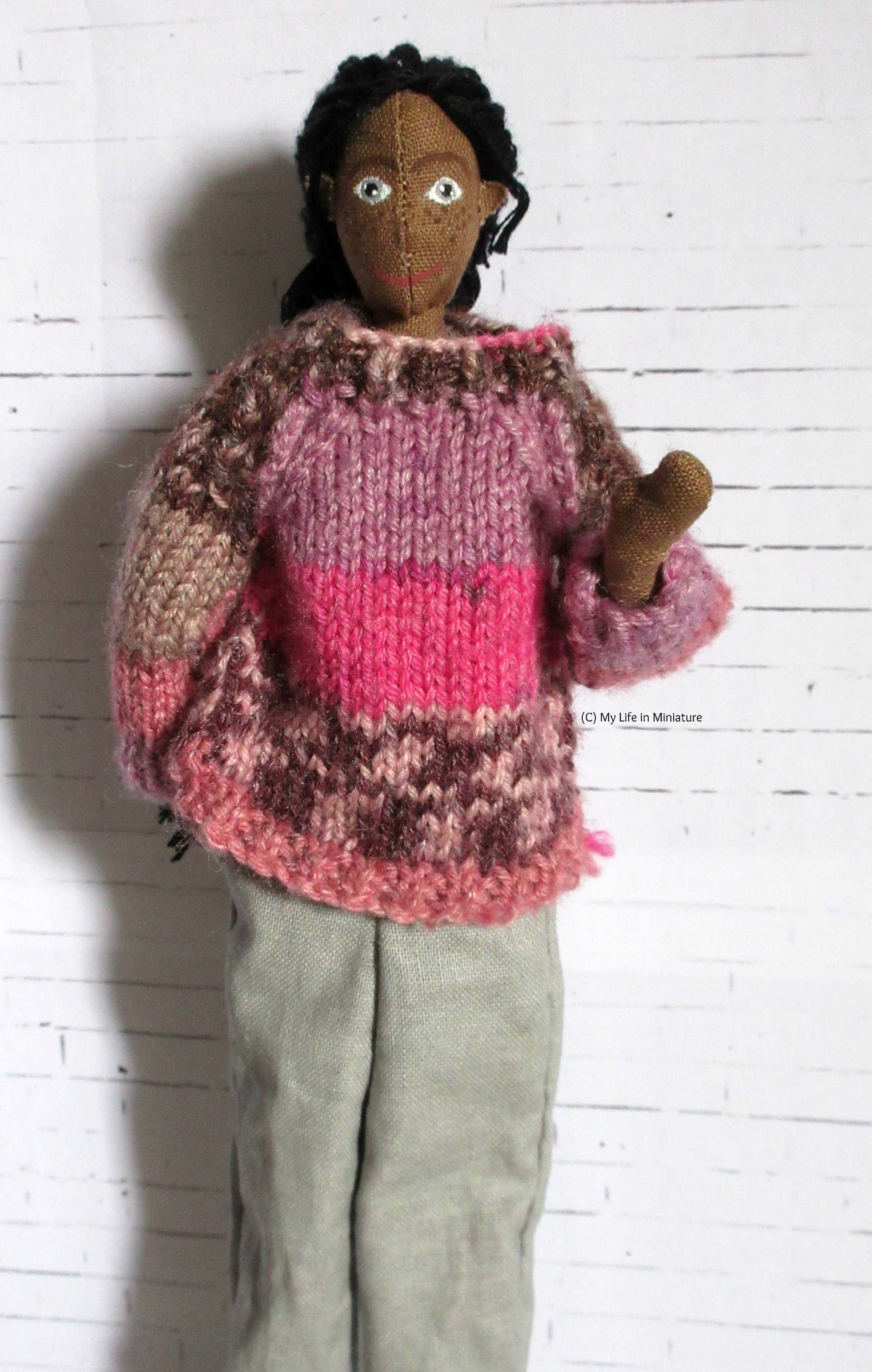 Petra stands against a white brick background. She has brown skin, grey eyes, freckles, and black hair. She wears a pink and purple jumper, loose grey pants, and is waving at the camera.