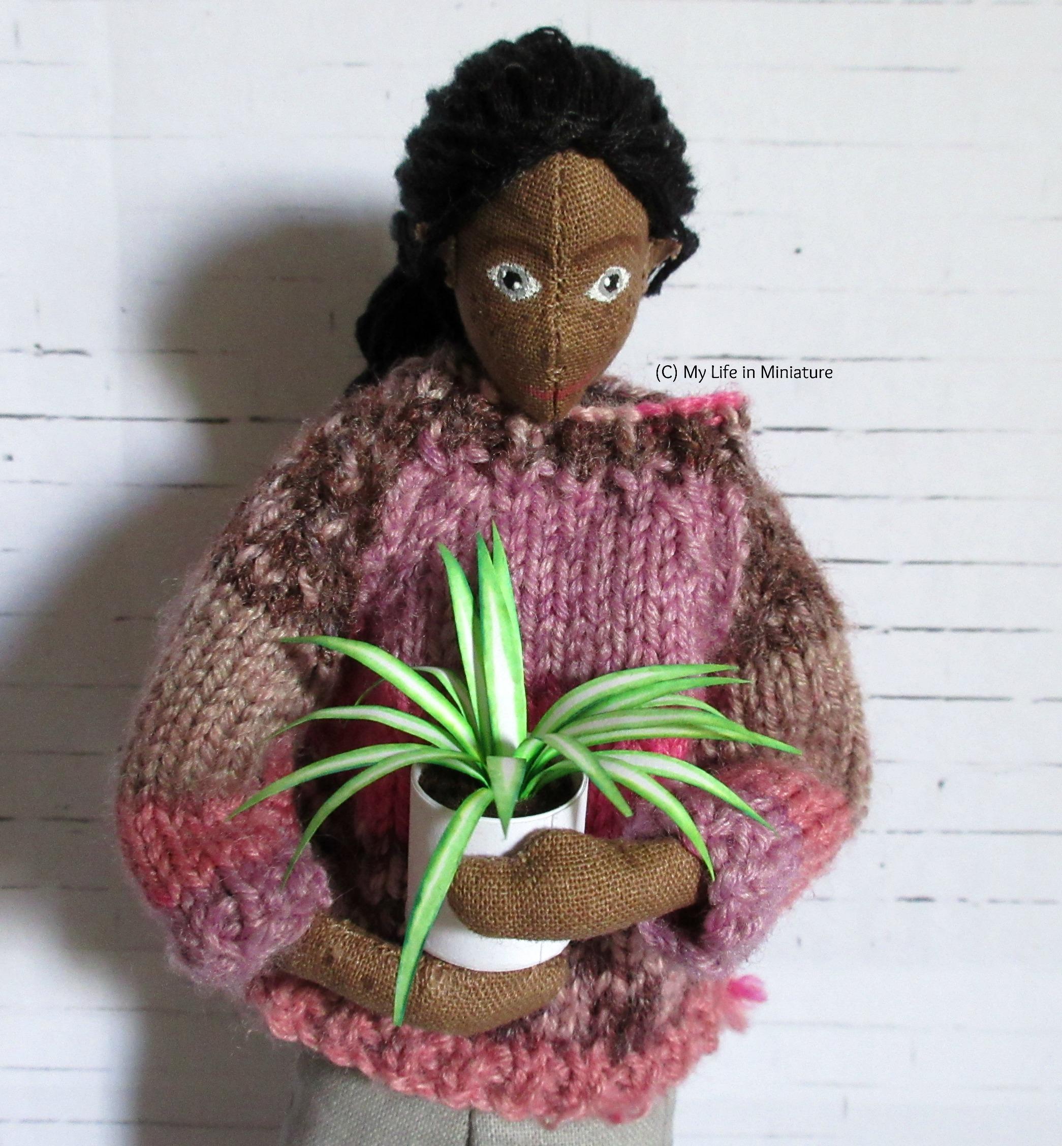 Petra holds a spiderplant in her arms, looking down at it. She's against a white brick background.