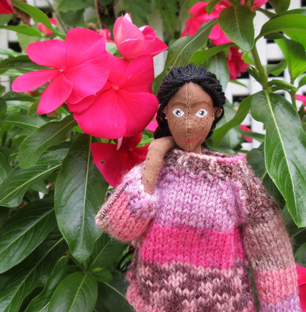 Petra wears a pink and purple knitted jumper, and is beside some hot pink flowers that match her jumper. One hand is on her shoulder and she looks at the camera.