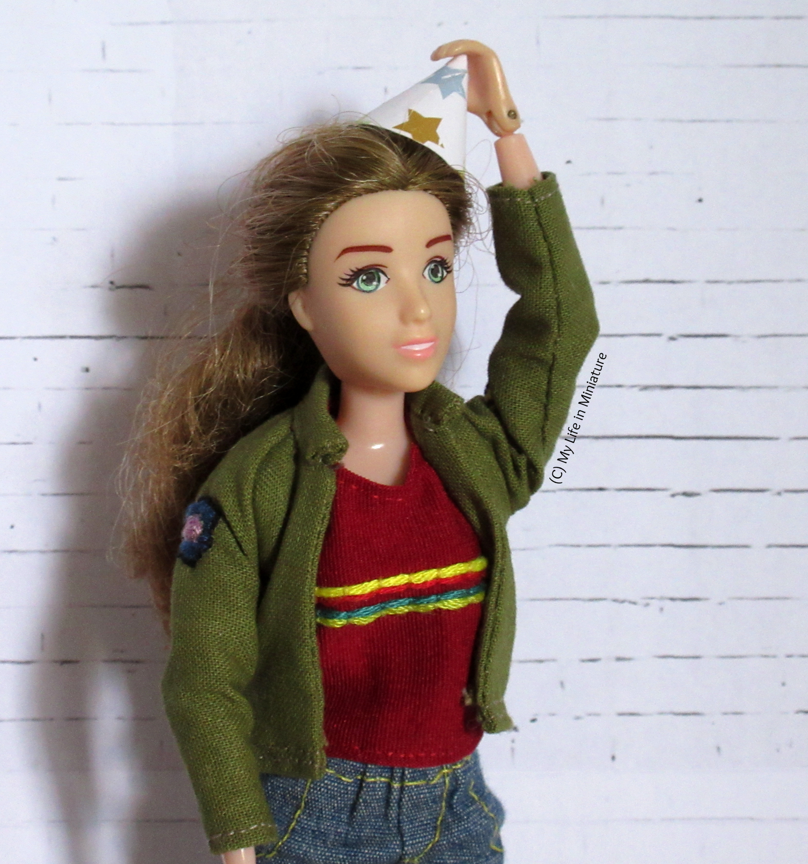 Sarah looks off into the middle distance, holding a small party hat on her head. She's in a khaki jacket, a red striped shirt, and jeans.
