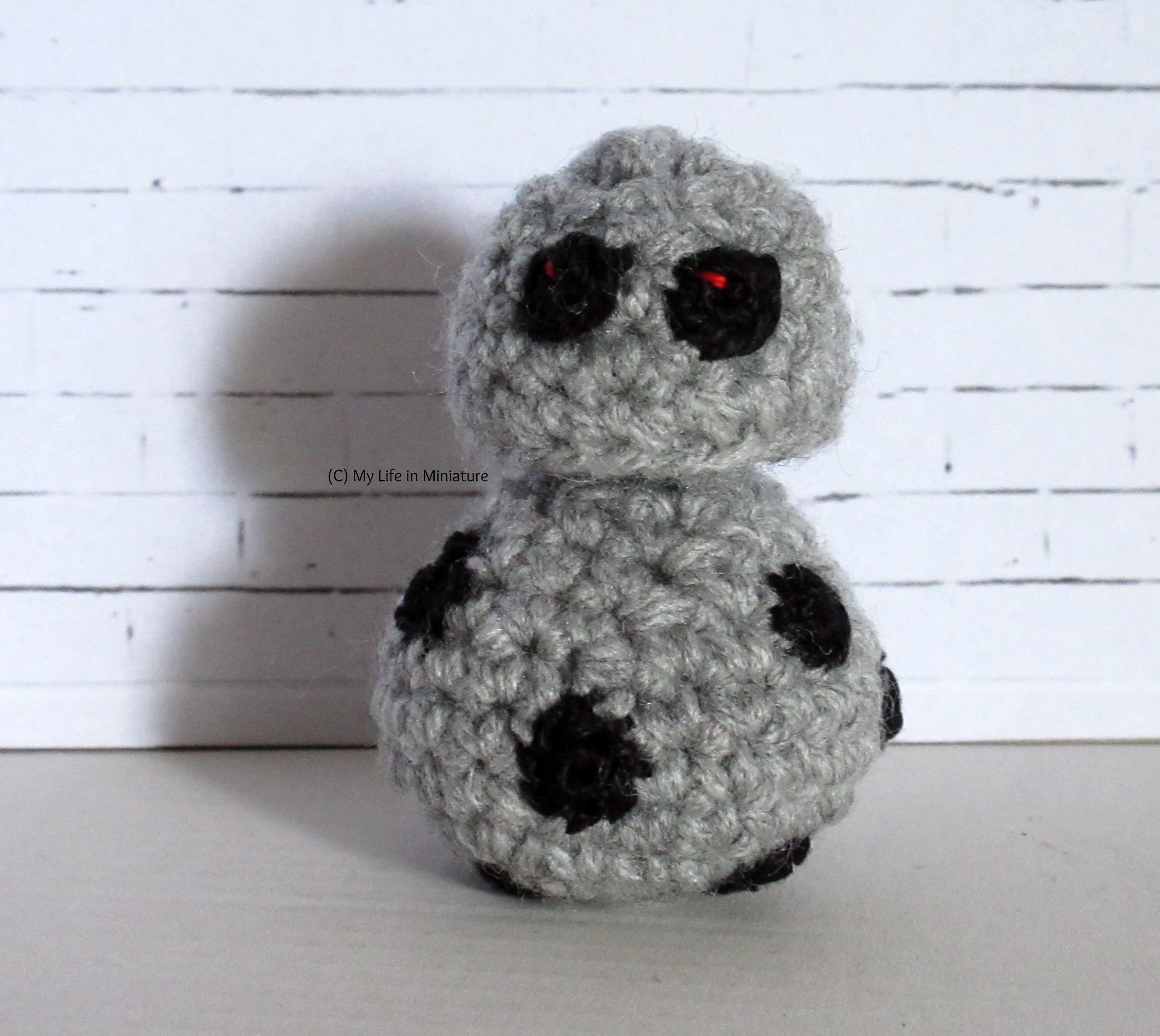 A small android sits against a white brick background. They are the same silhouette as BB-8, but grey with more small black function openings on their body. They have two optical sensors on their head, both looking at the camera.