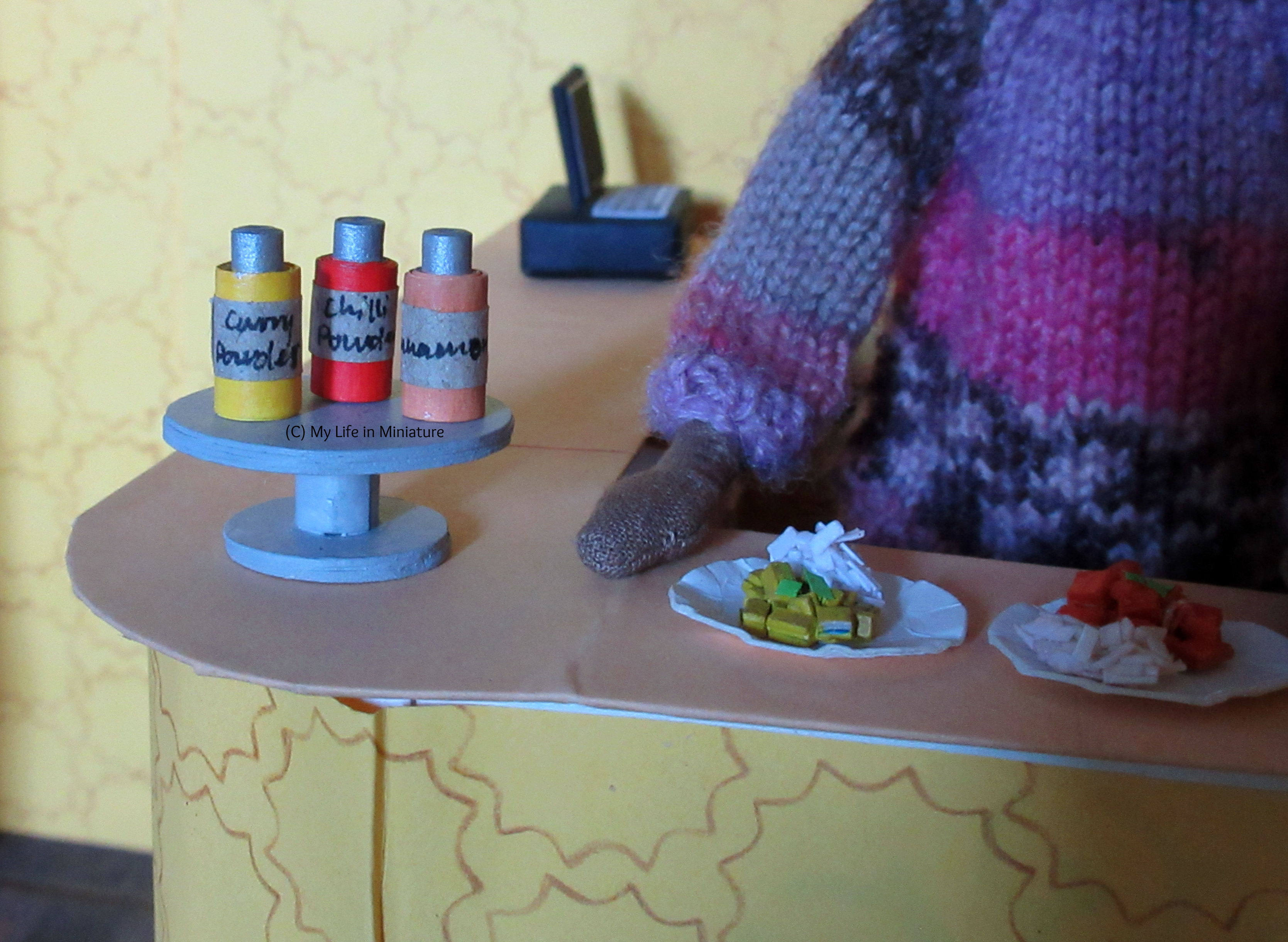 The silver cake stand is on the Tea at Yaz's counter, with the three jars on top. The curry powder jar is yellow; the chilli powder jar is red; the cinnamon jar is pale brown.