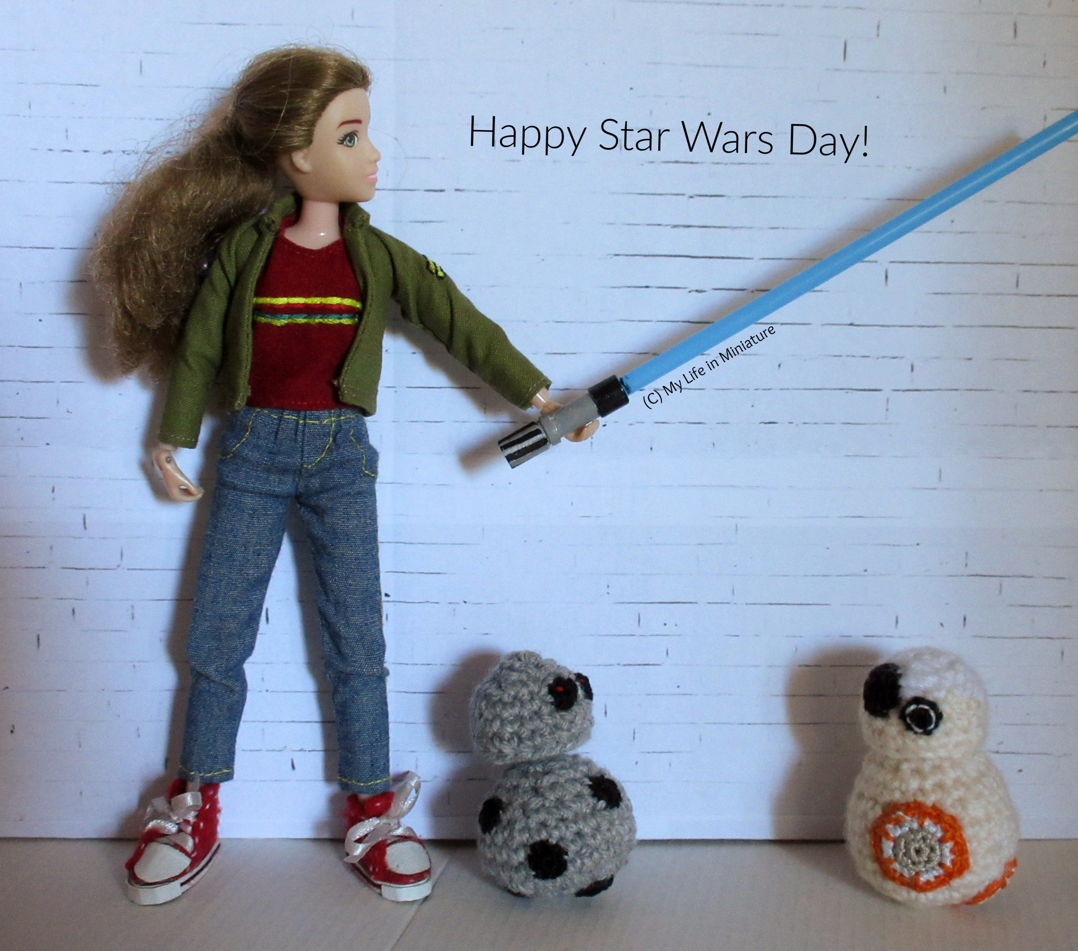 Sarah, BB-8, and Chip stand against a white brick background. Sarah is holding a blue lightsaber out to her side, looking at the laser. Chip and BB-8 are at Sarah's feet, looking at each other. Above the lightsaber are the words 'Happy Star Wars Day!'.