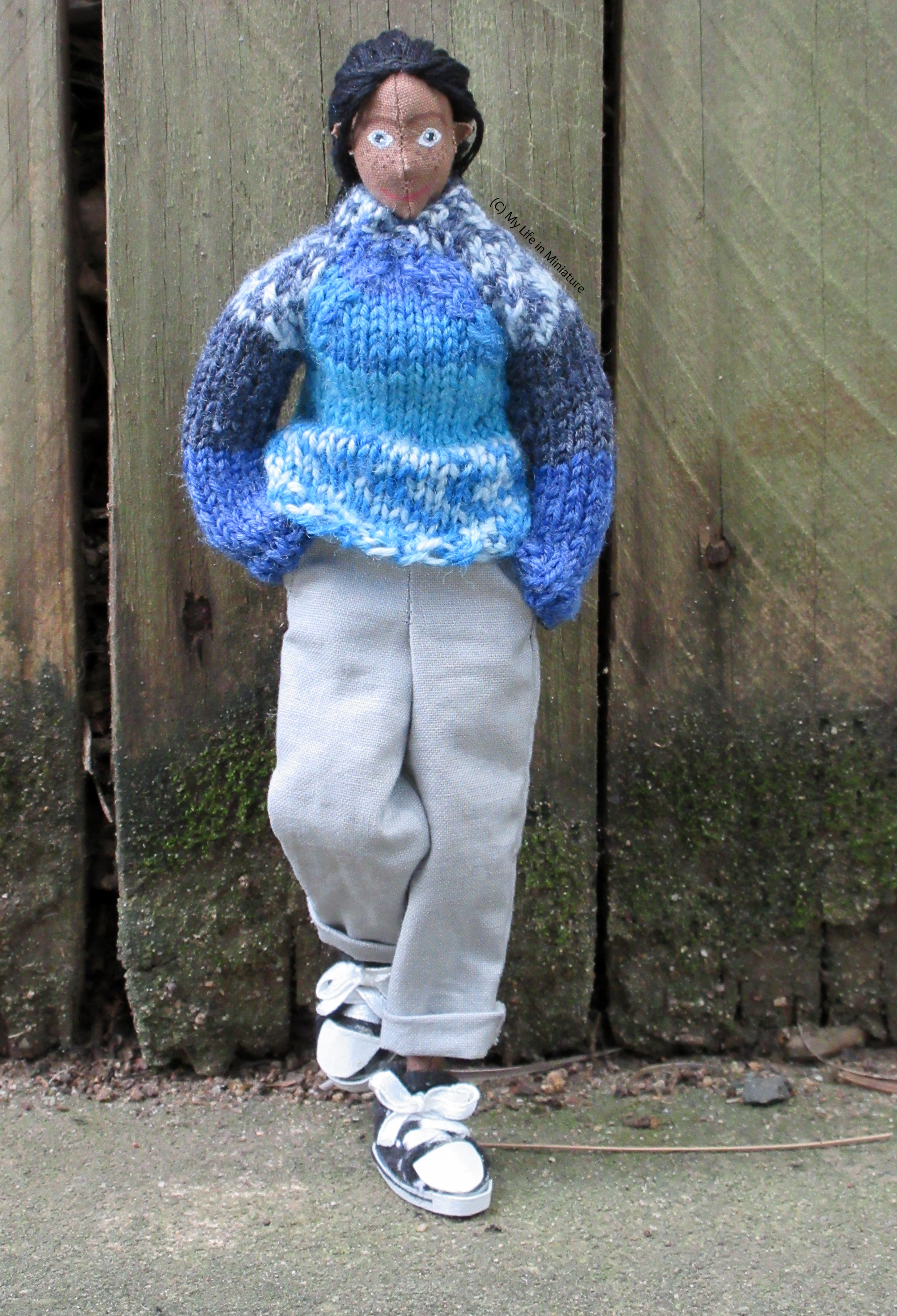 Petra stands against a fence, hands in pockets and foot propped up. She wears the blue jumper and loose grey pants with black Converse high-tops. She's looking at the camera.