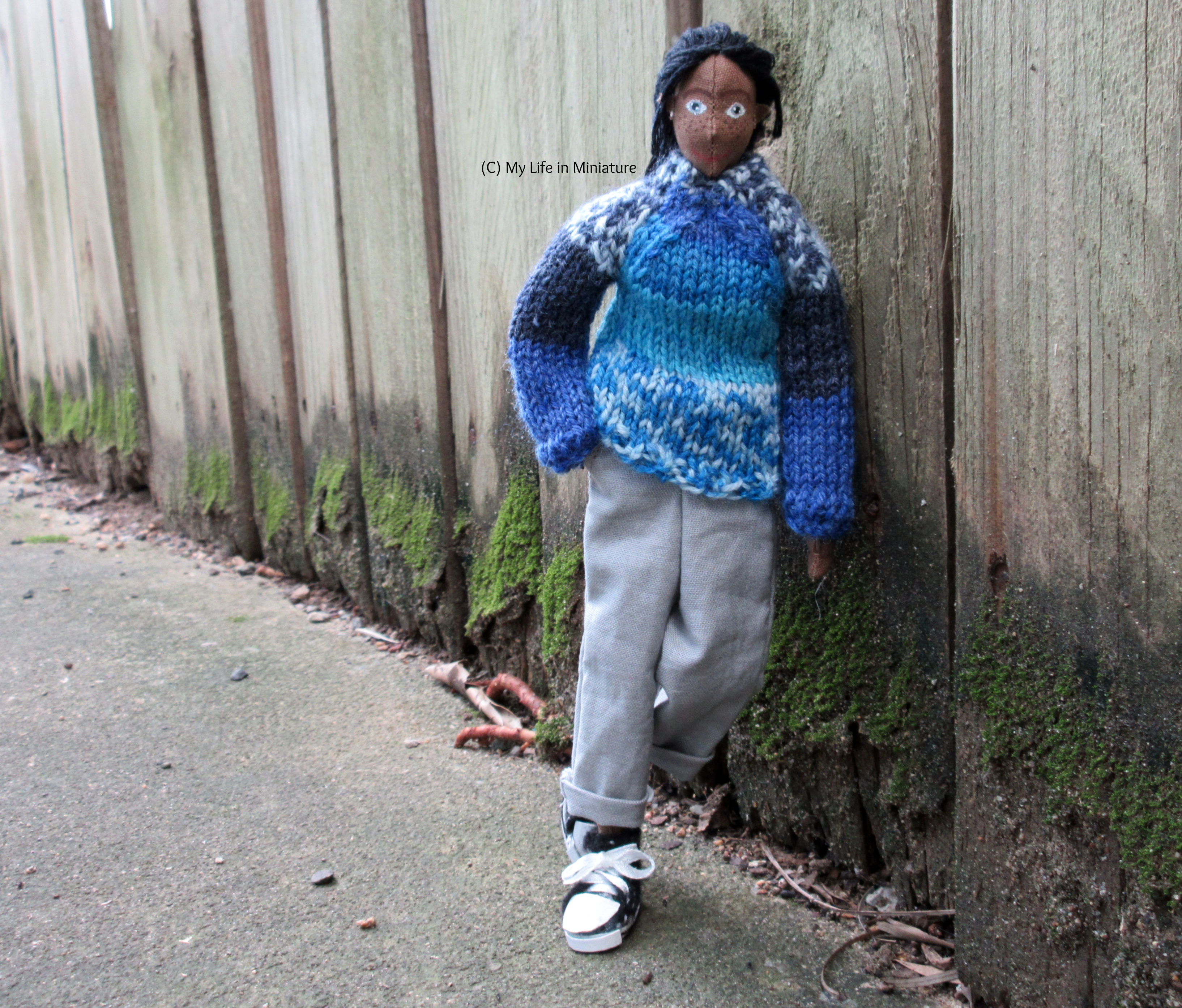 Petra leans a shoulder against a wooden fence, one hand in her pocket and one foot propped up. She's looking at the camera, wearing the blue jumper, grey pants, and black shoes.