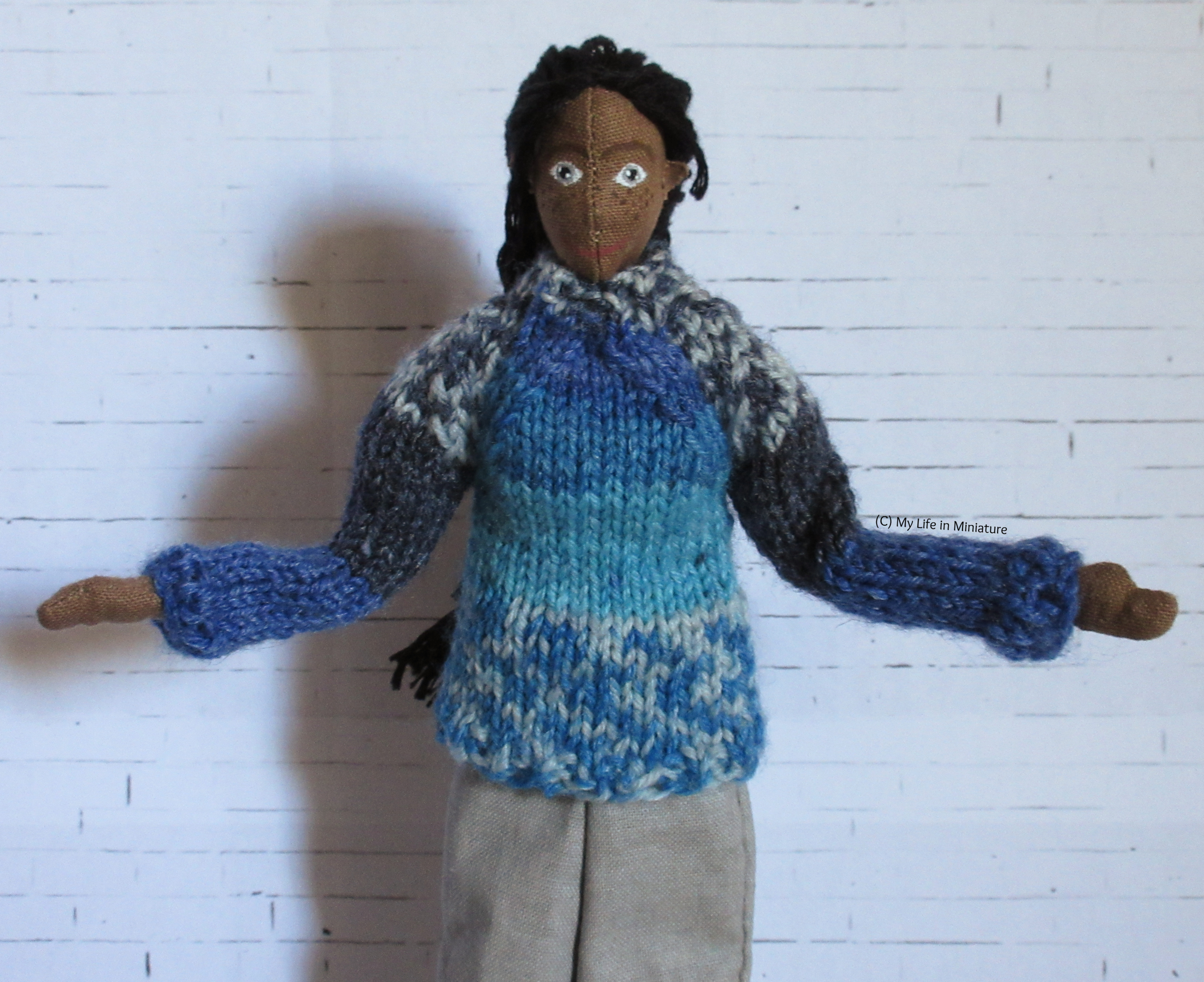 Petra stands against a white brick background, arms out in a 'look at my outfit' pose. She wears a knitted jumper in various shades of blue and loose grey pants.