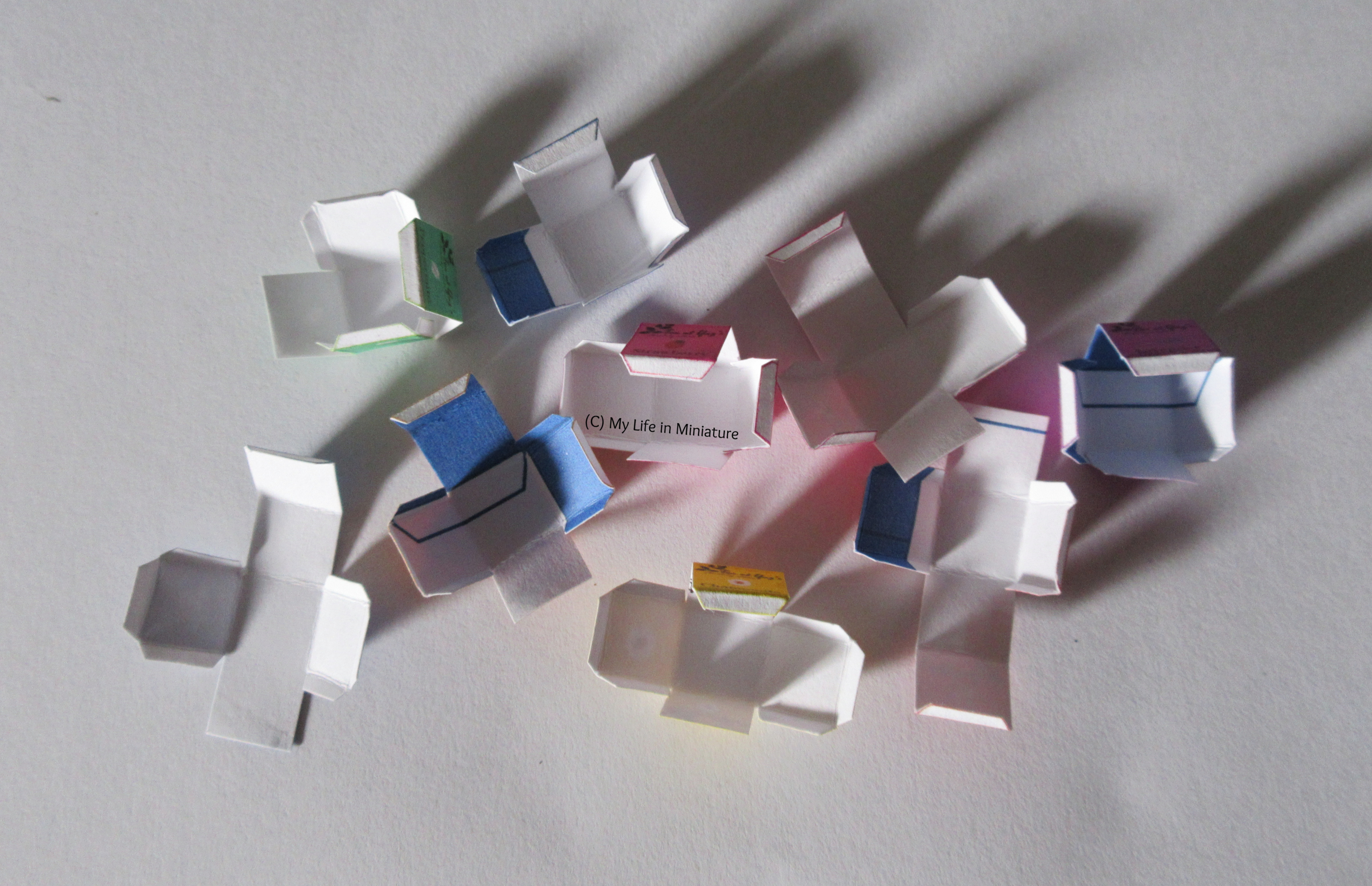 Nine small boxes sit in an unfinished state on a white background. What's on them is unclear.
