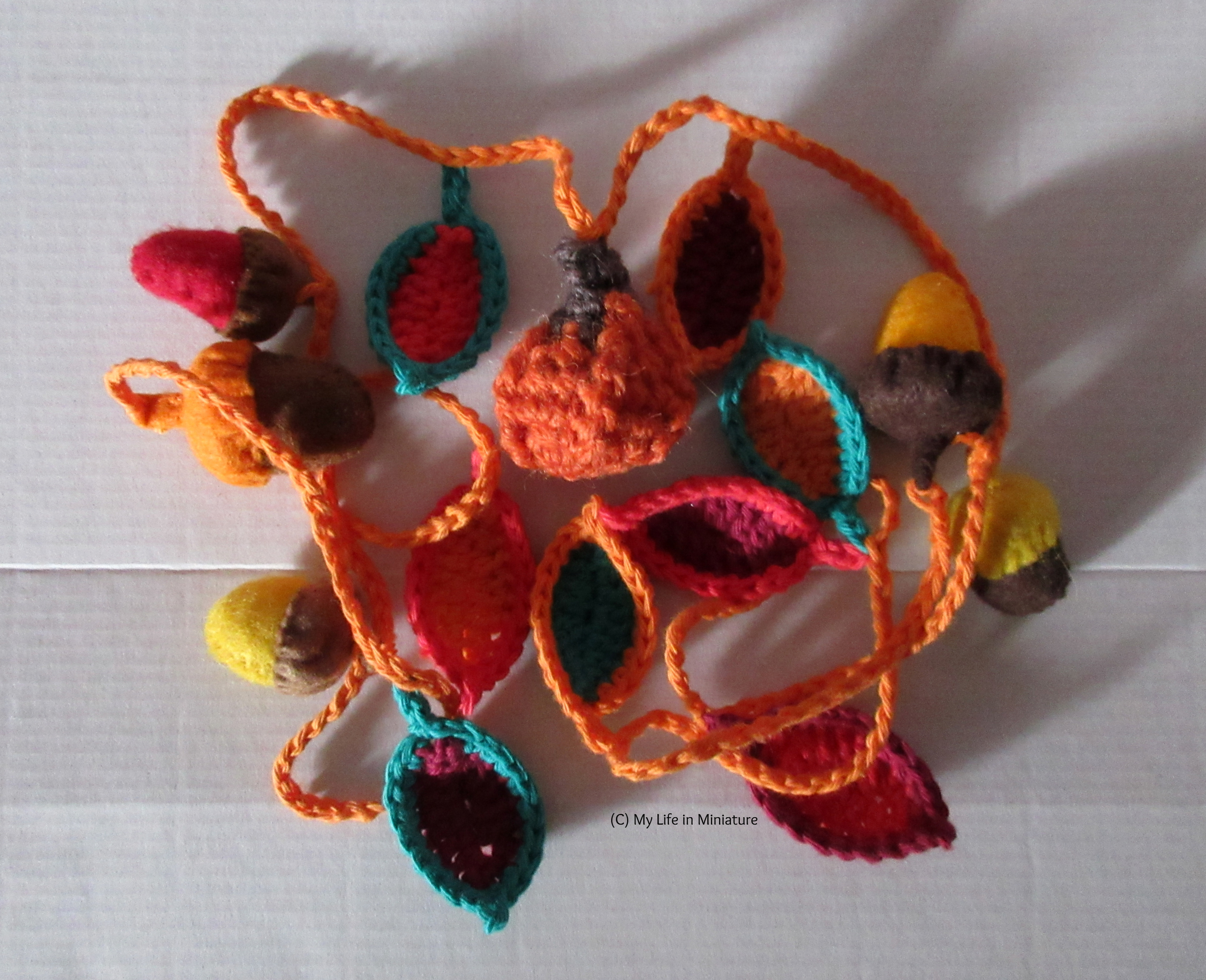 An autumnal garland sits in a pile on a white background. Felt acorns are visible, as well as crocheted leaves in various shades of green, red, and orange, and a small crocheted pumpkin.