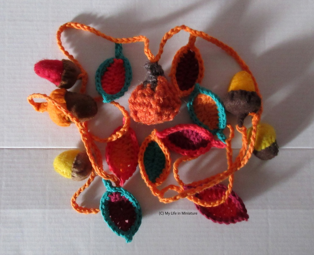 A crocheted garland sits in a pile on a white background. A pumpkin is visible, as are felt acorns in shades of yellow, orange, red and brown. There are also crocheted leaves in various shades of green, red, and orange, all attached to each other with an orange yarn chain.