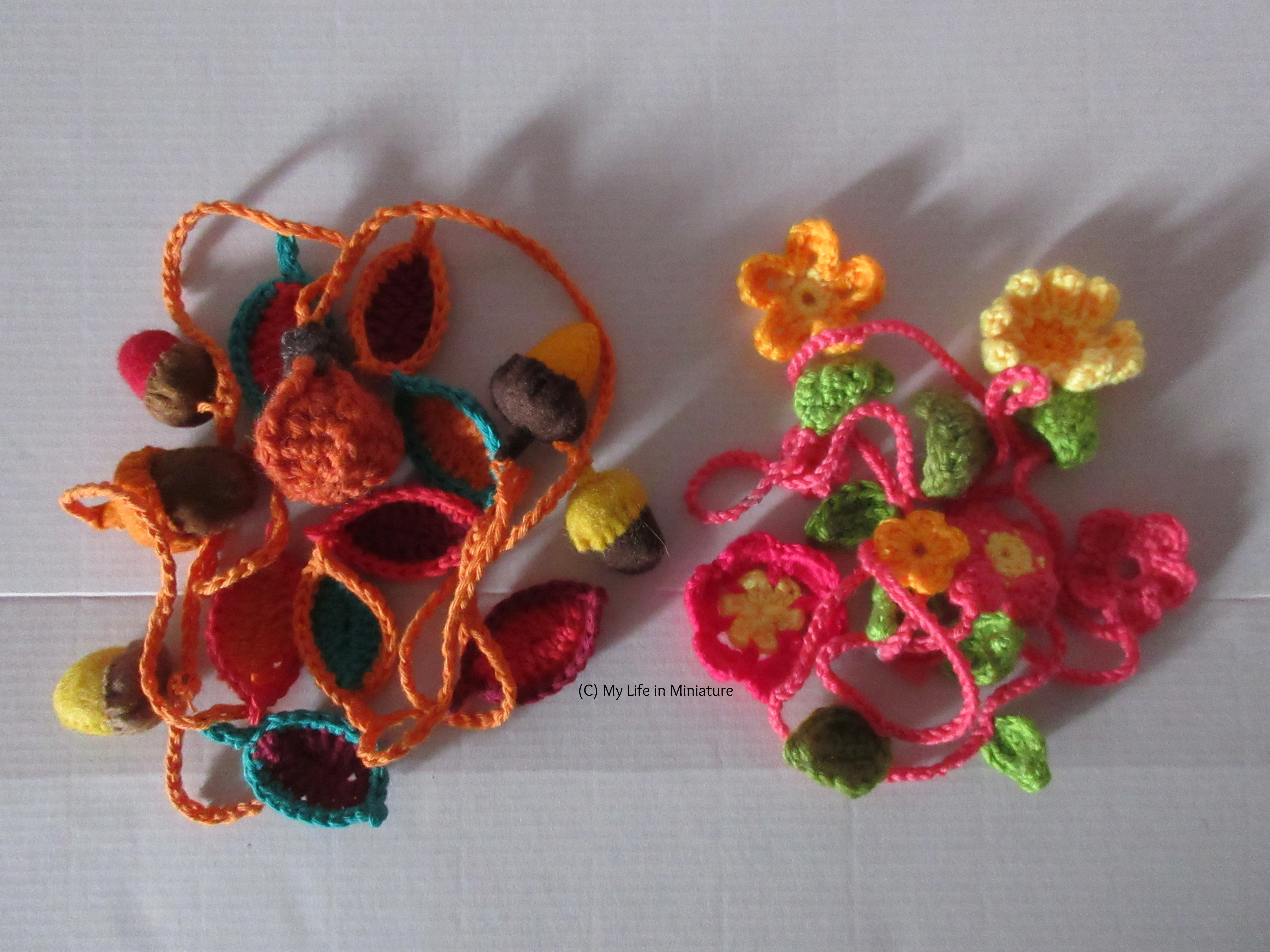 The autumn garland sits in a pile next to a pink floral spring garland on a white background.