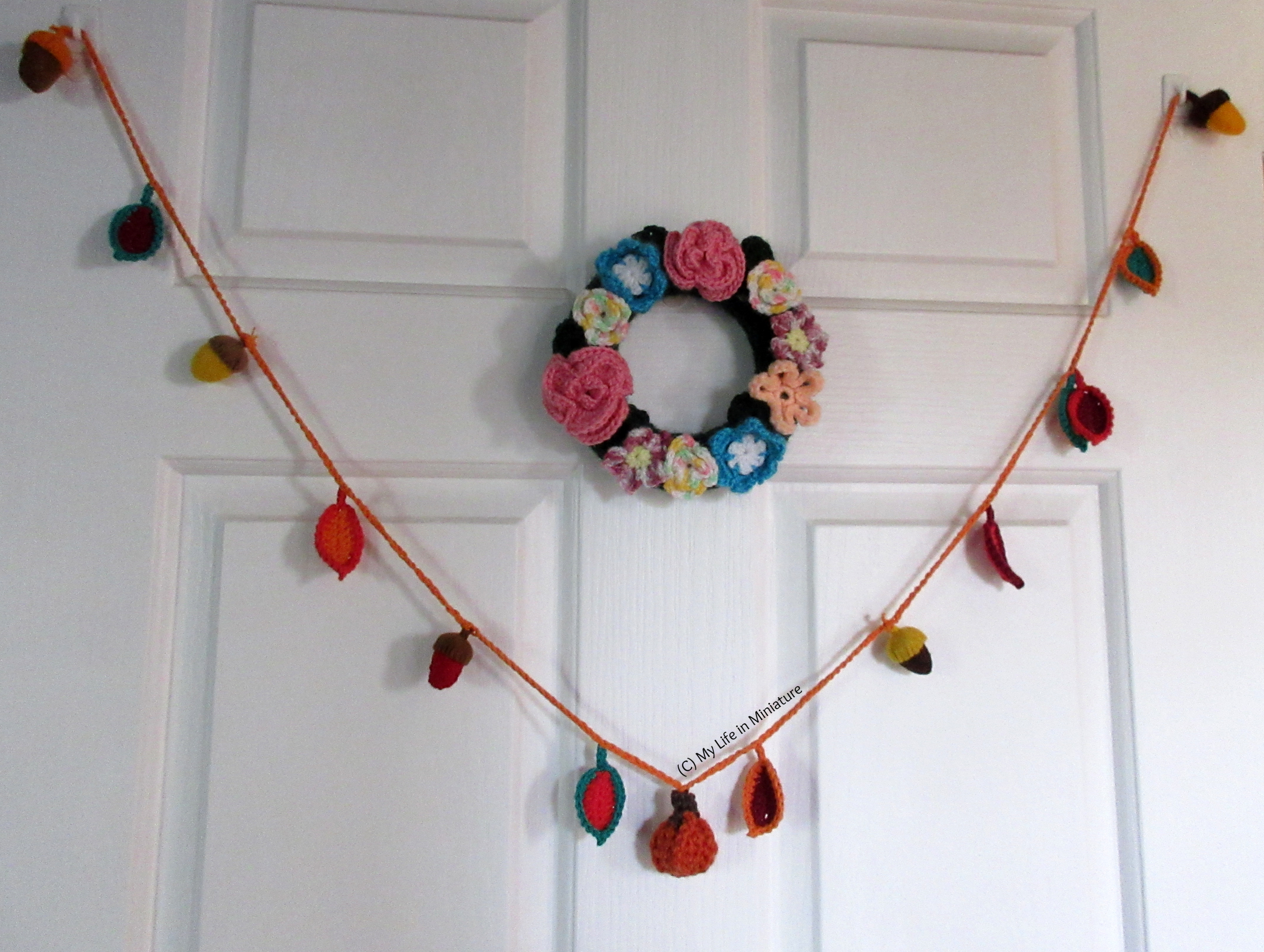 The autumn garland is hung on a door, pumpkin in the centre.