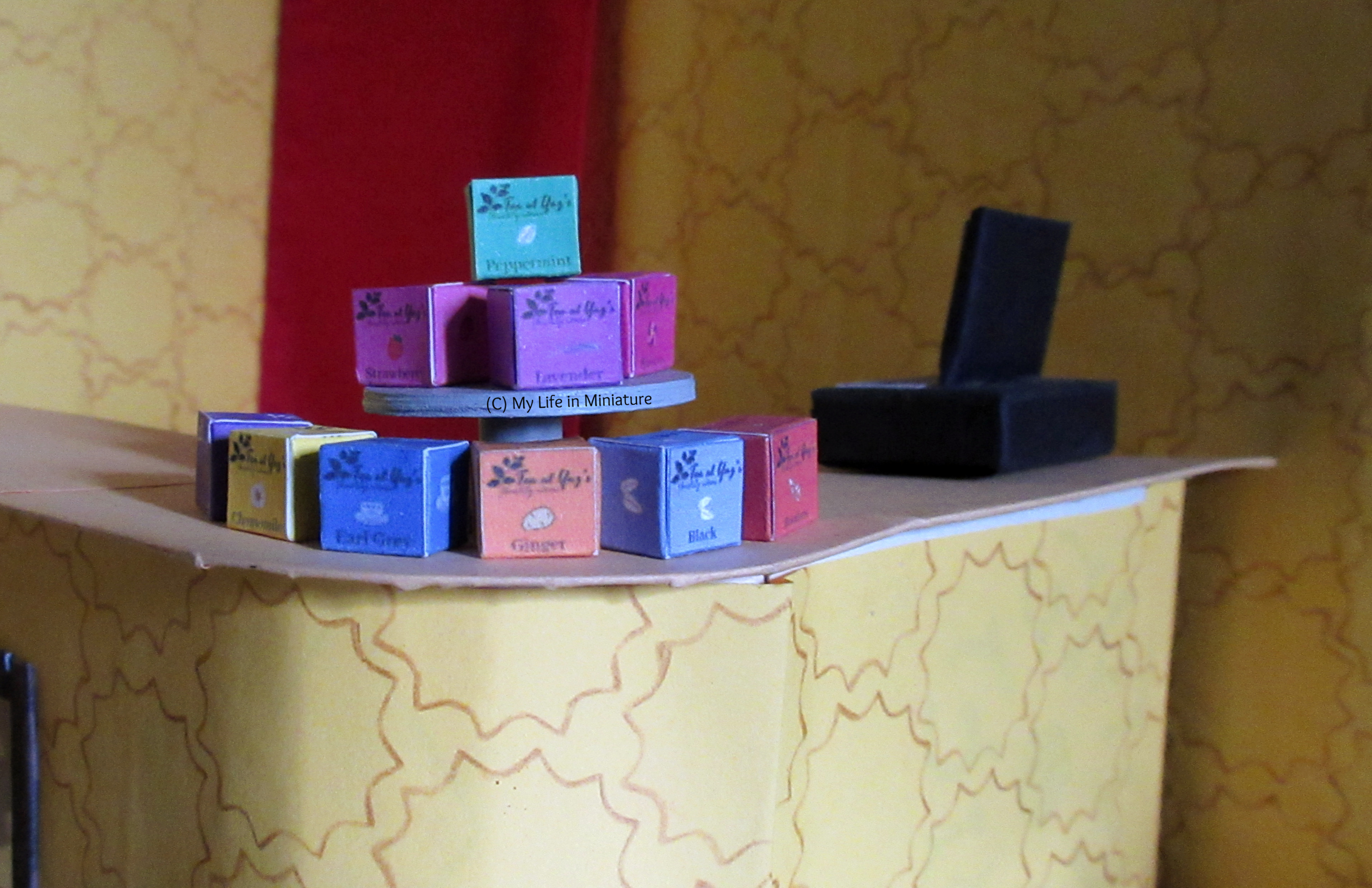 A stack of small square boxes in various colours are on the cake stand in Tea at Yaz's; on the curved counter.