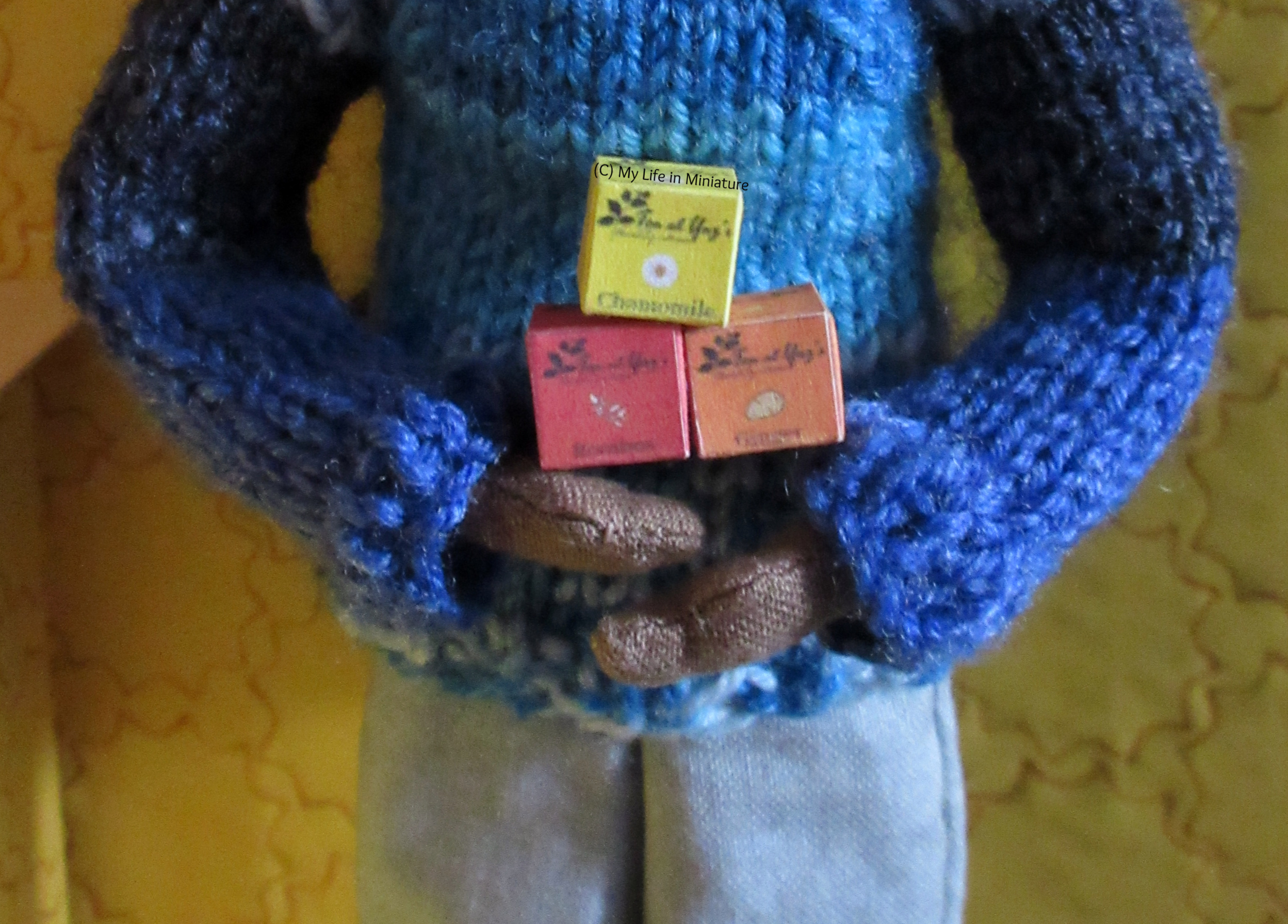 Petra holds three of the boxes in her hands, in front of her blue jumper.