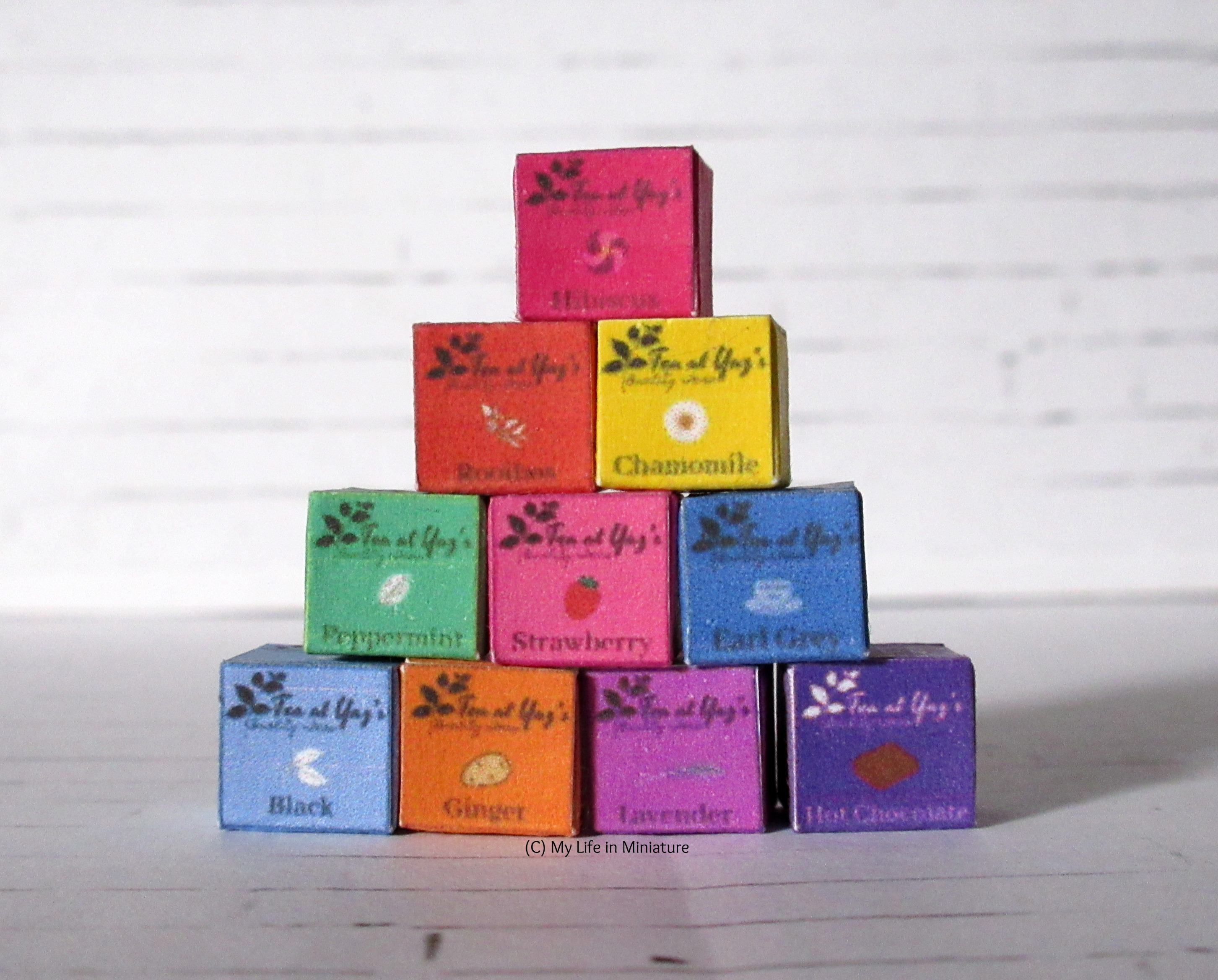 Ten Tea at Yaz's boxes are stacked in a tower against a white brick background. The different types of tea they contain are visible on the front of the boxes (plus one box of hot chocolate in the bottom right).