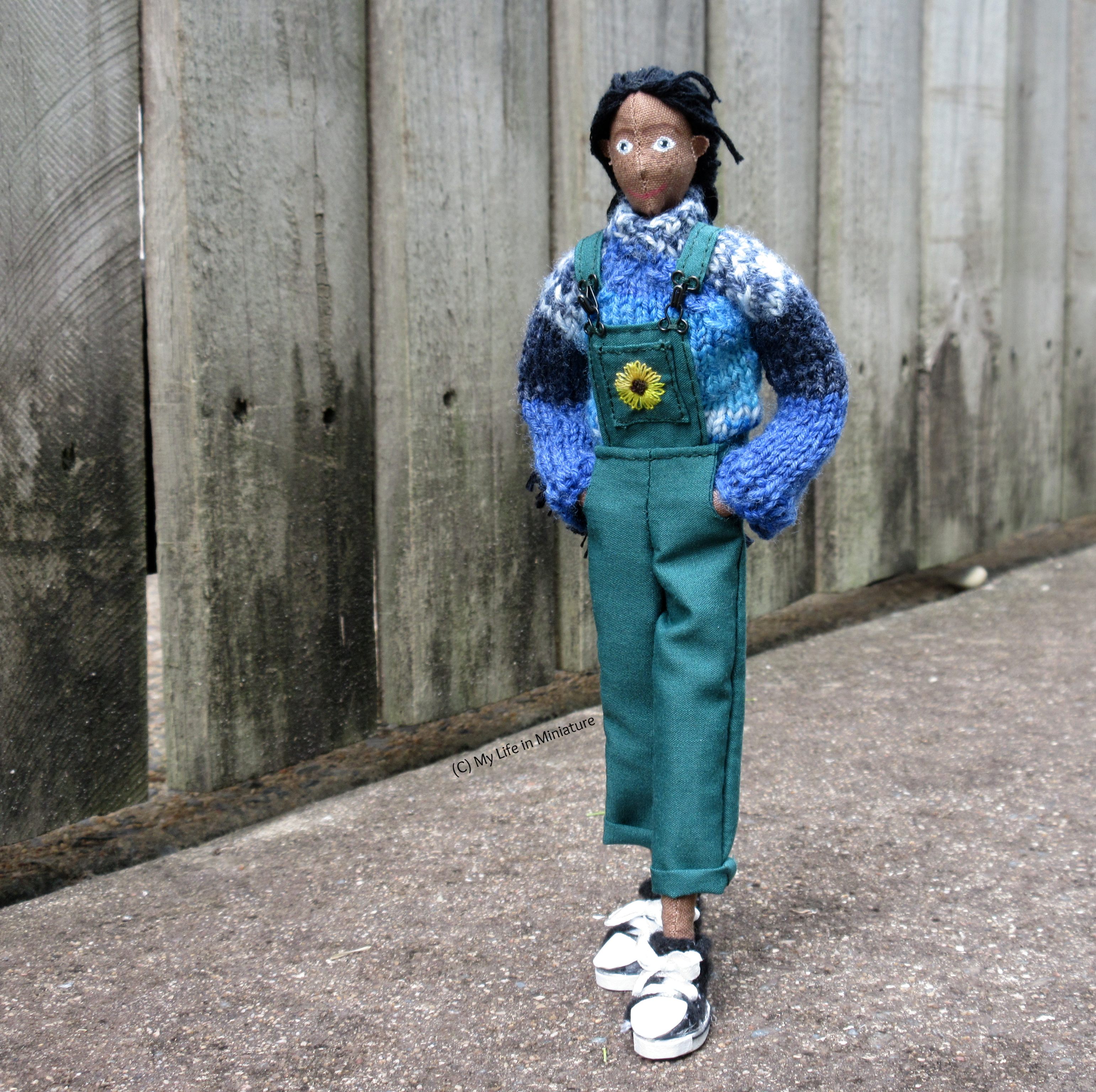 Petra walks past the camera to the left, with a wooden fence in the background. Her hands are in the side pockets of her green dungarees, and she wears her blue jumper and black high-top Converses.