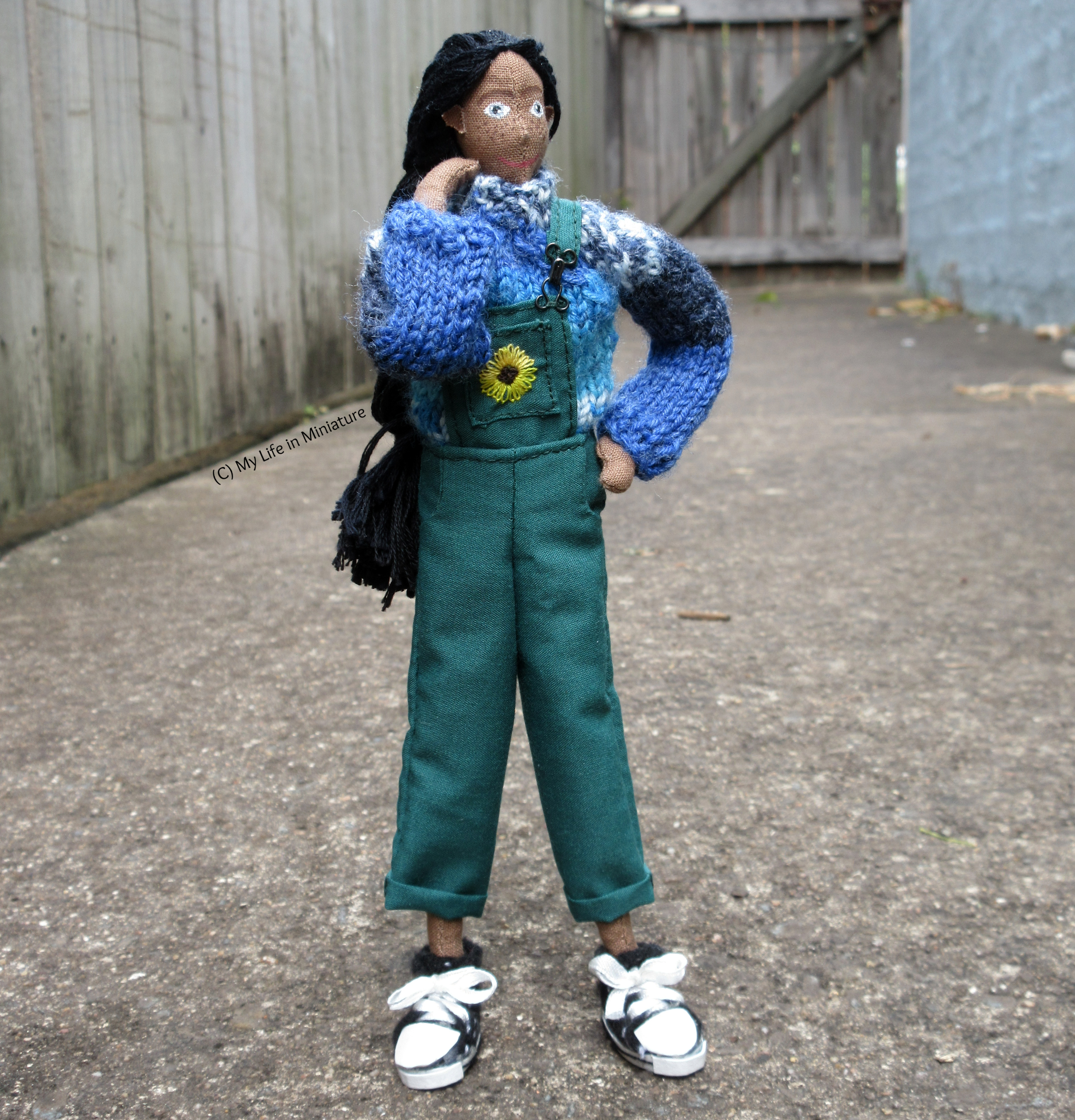Petra stands with legs apart, one hand on her hip and one on her shoulder. She looks to the right; wearing her long green dungarees with her blue jumper and black shoes. Behind her is a wooden fence and wooden gate.