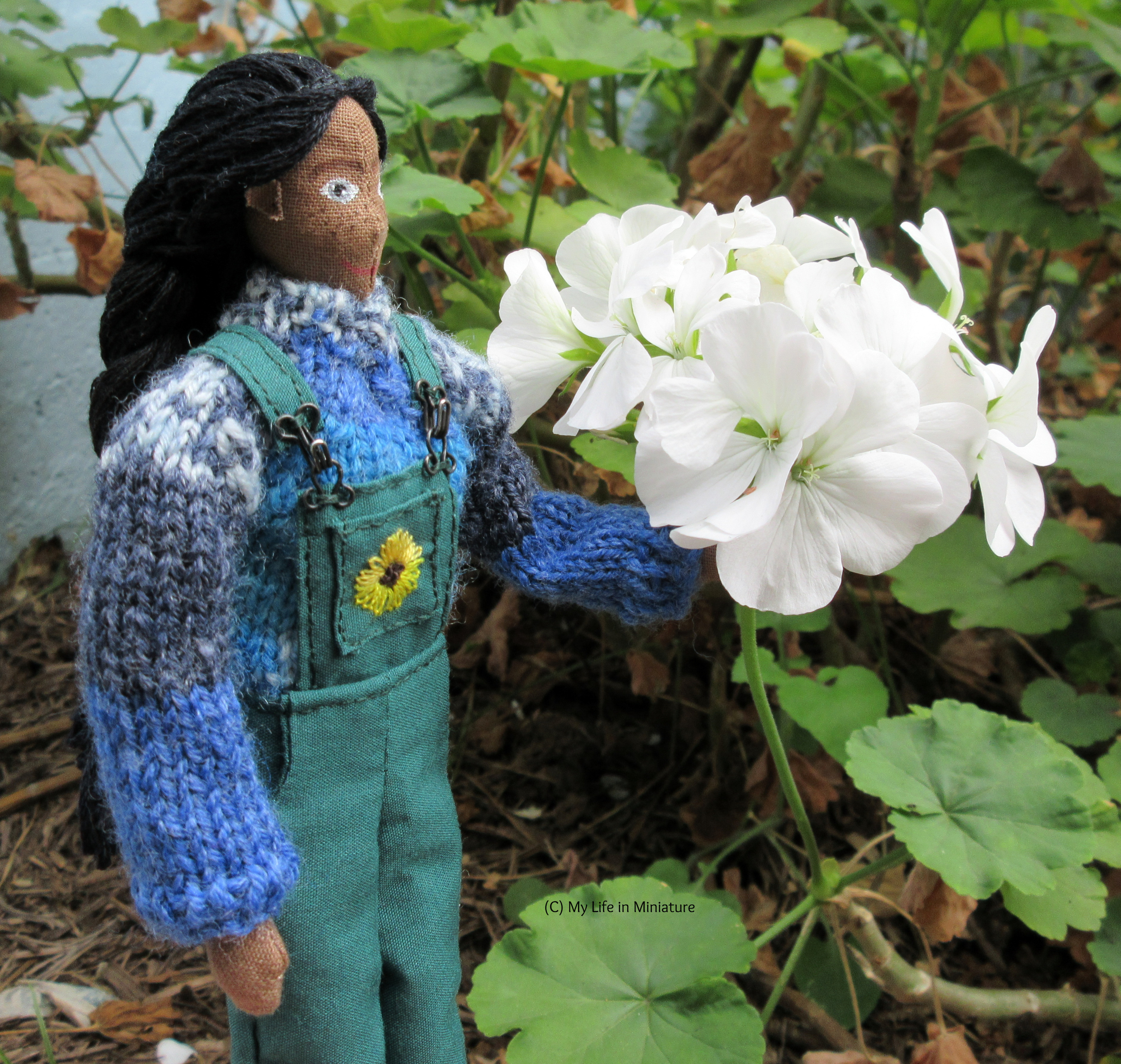 Petra stands next to a large white geranium flower, one hand on the stem. She's looking at it, wearing the green dungarees and blue jumper.