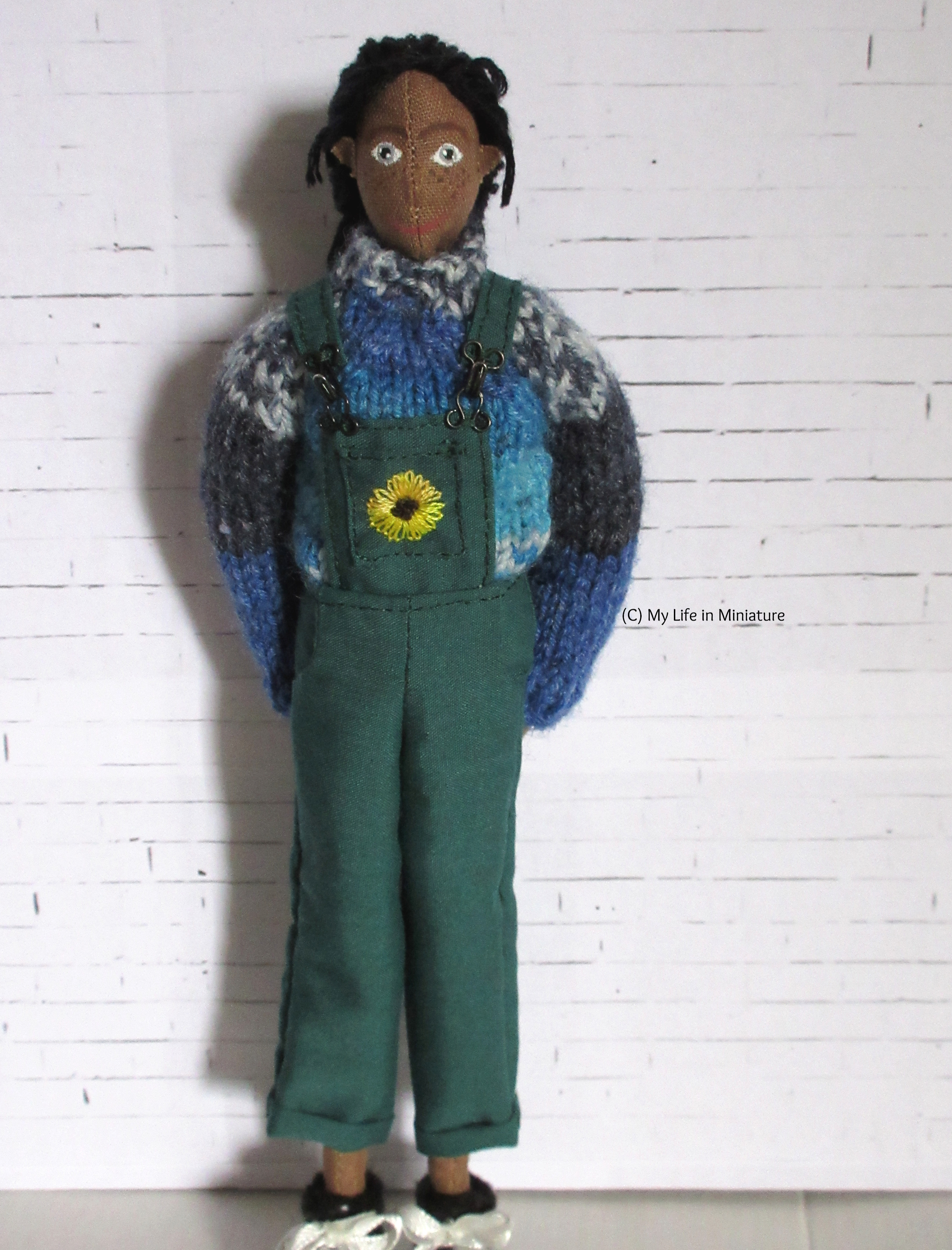 Petra stands in front of a white brick background, smiling at the camera with her hands behind her back. She wears a pair of long green dungarees that have a sunflower embroidered on the pocket, and her blue jumper.