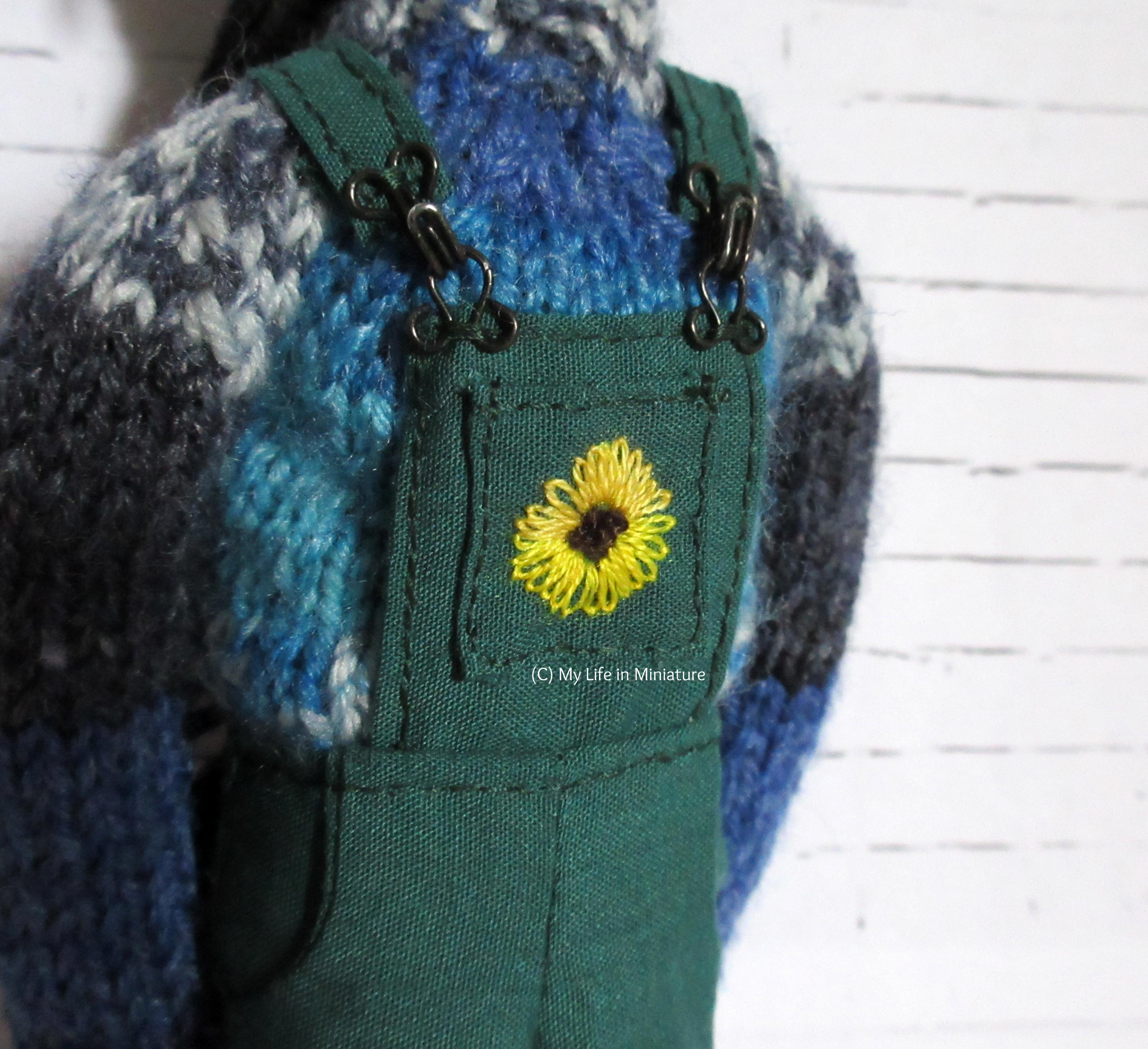 Close-up of the sunflower embroidered on the front pocket of the dungarees.