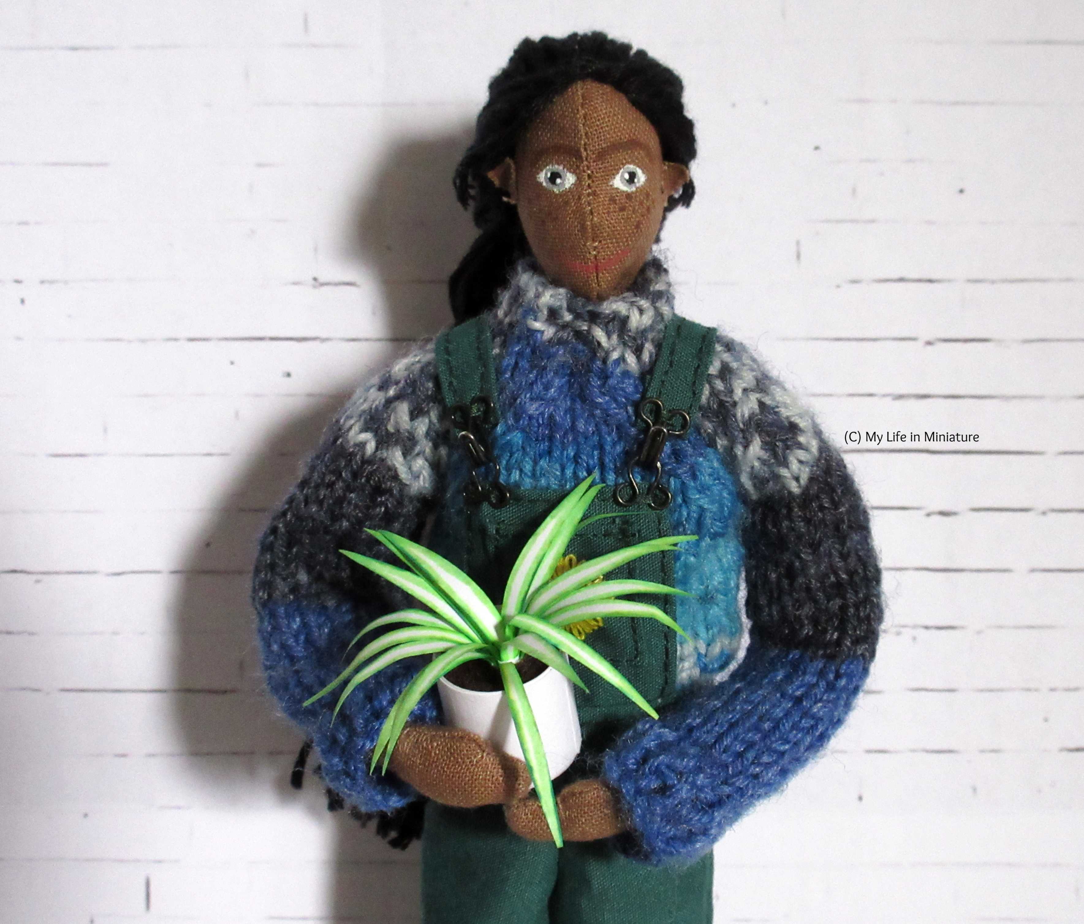 Petra holds a spider-plant wearing the dungarees and jumper, smiling at the camera.