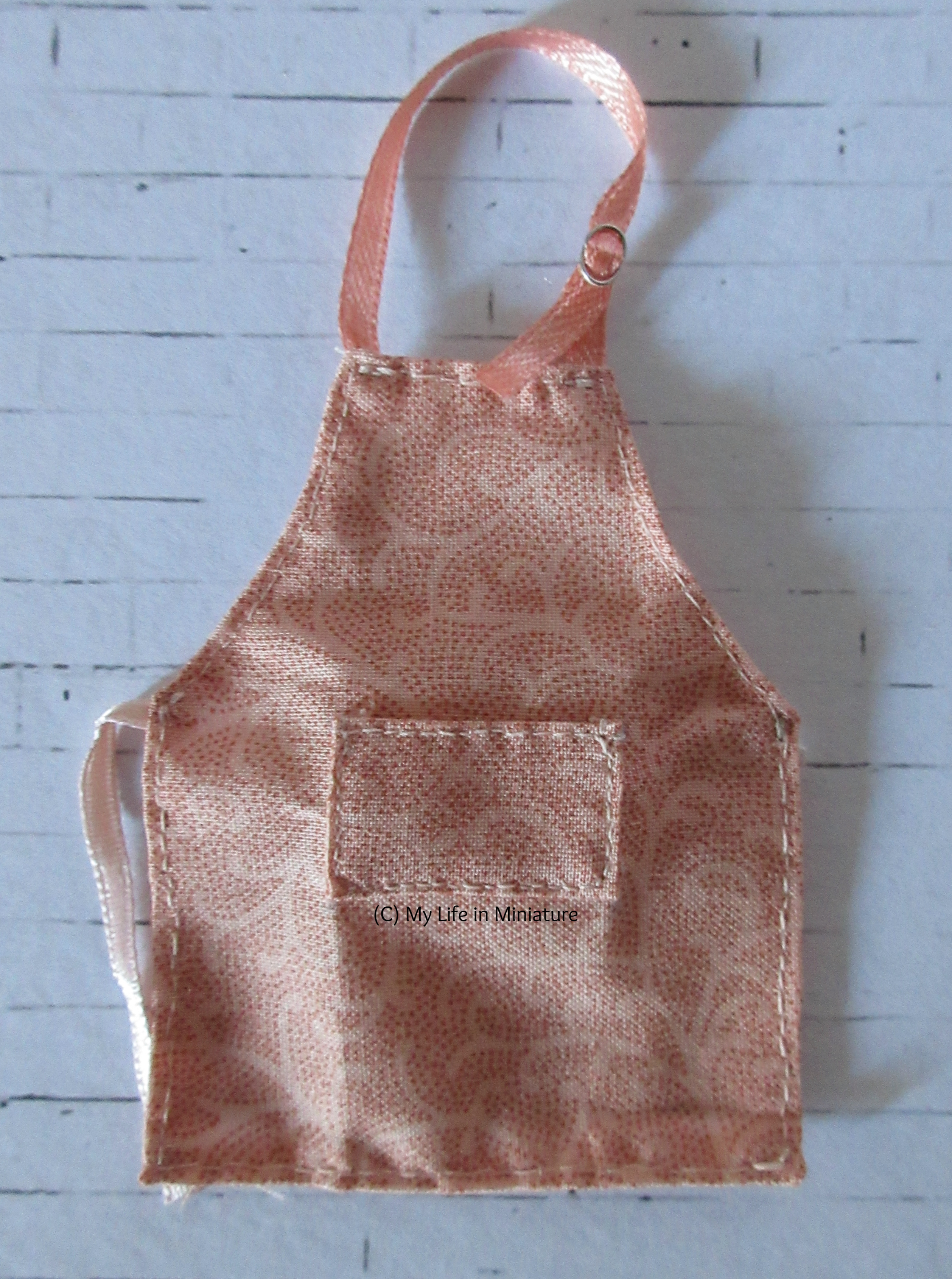 The pink apron sits on a white brick background.