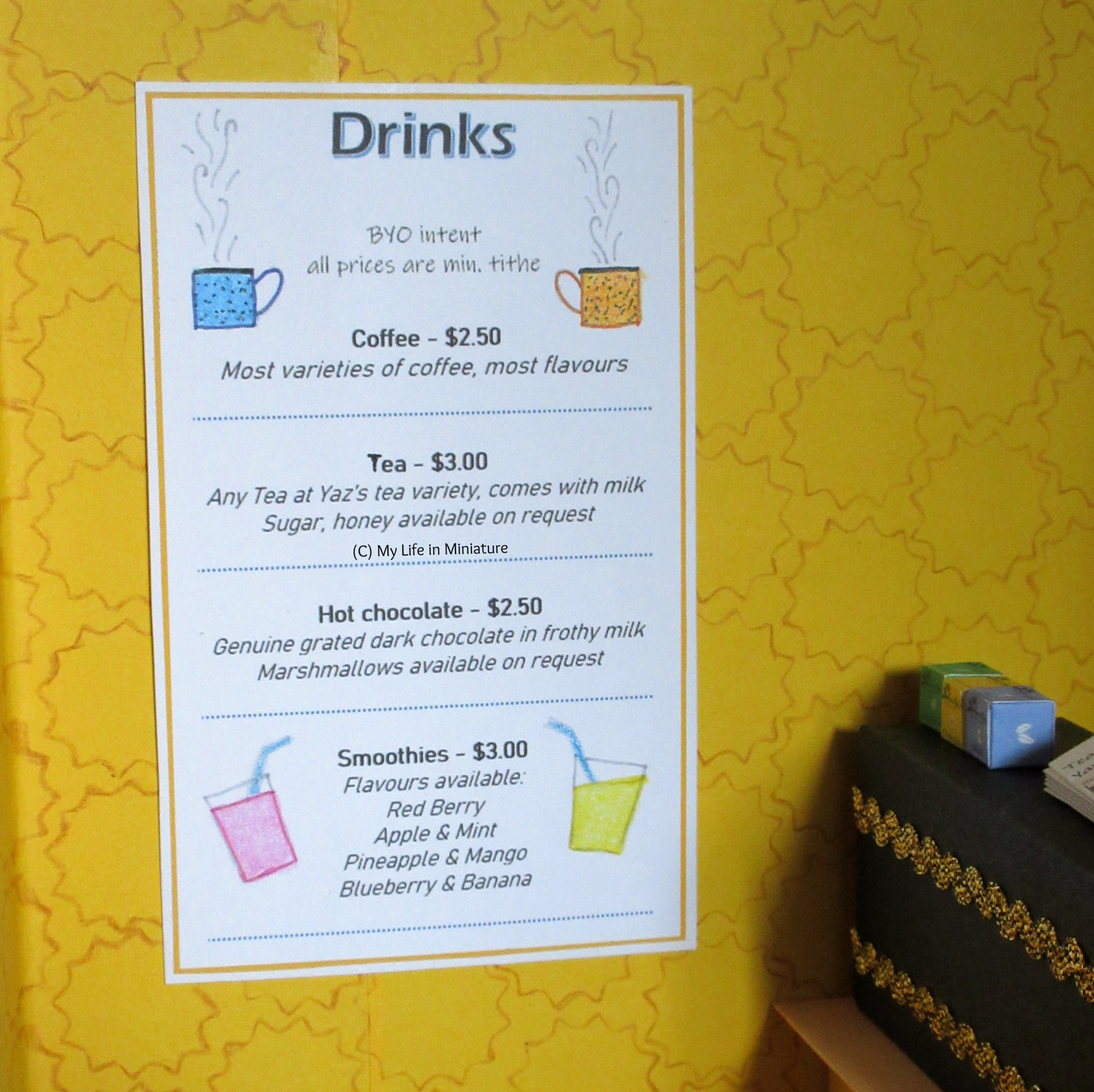 A drinks menu is on the wall of Tea at Yaz's, near the coffee machine. It lists the different drinks available, with their prices.