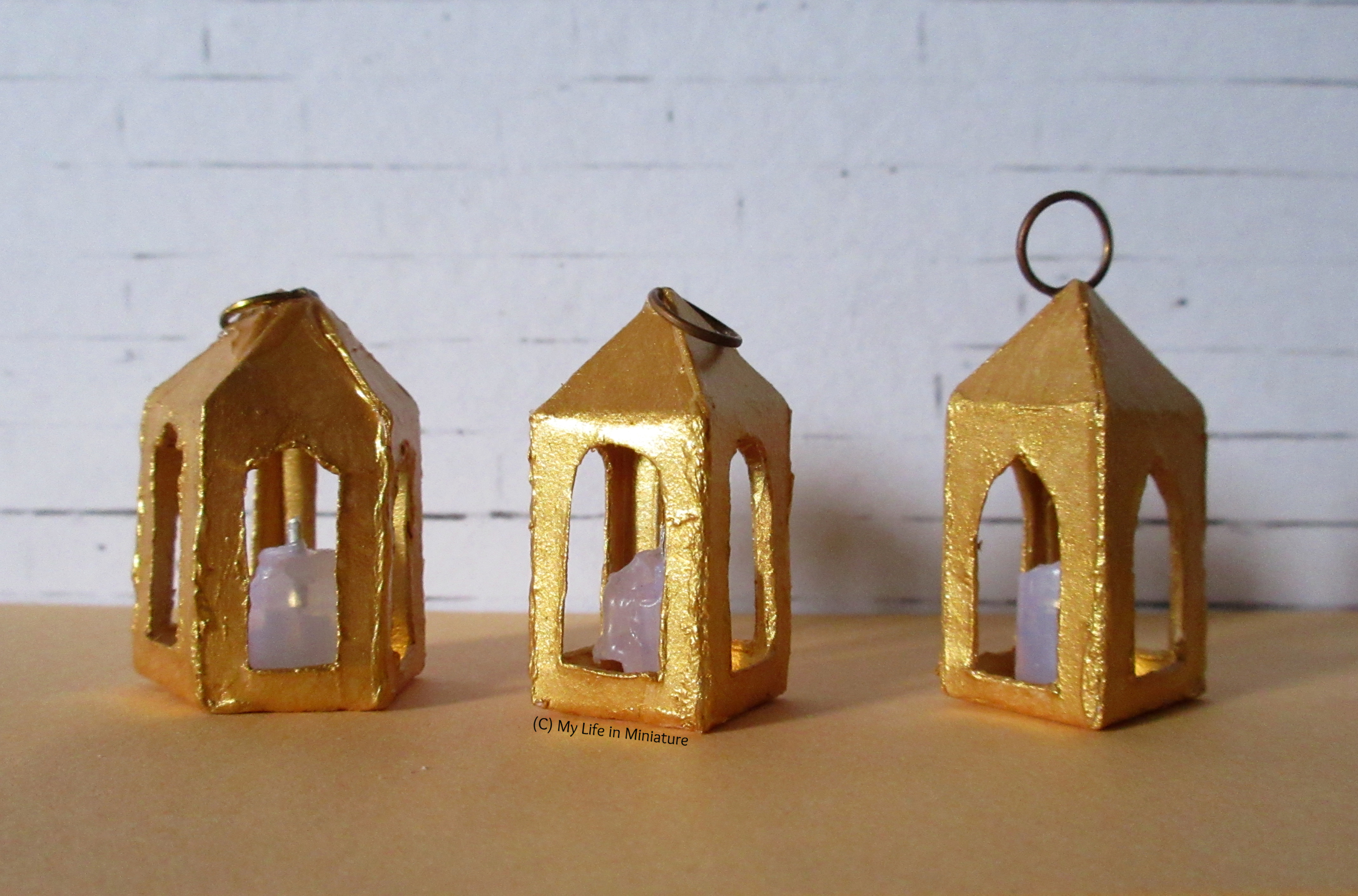 Three gold lanterns sit in front of a white brick background. A pentagonal one is on the far left, next to two square ones. One of the square ones has a ring that stands up. All three have candles inside.