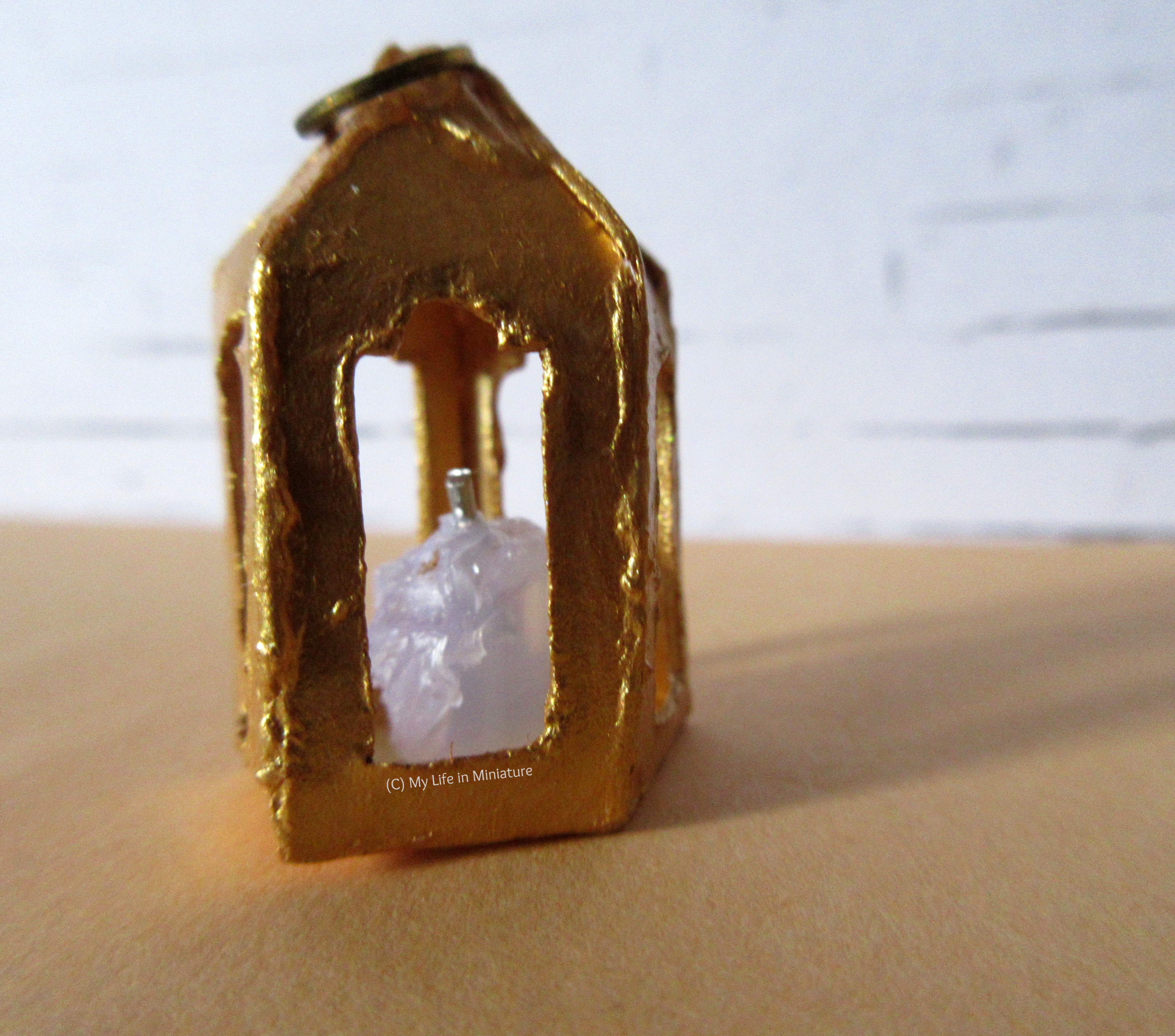 Close-up of the pentagonal lantern's candle, through one of the windows in the side.