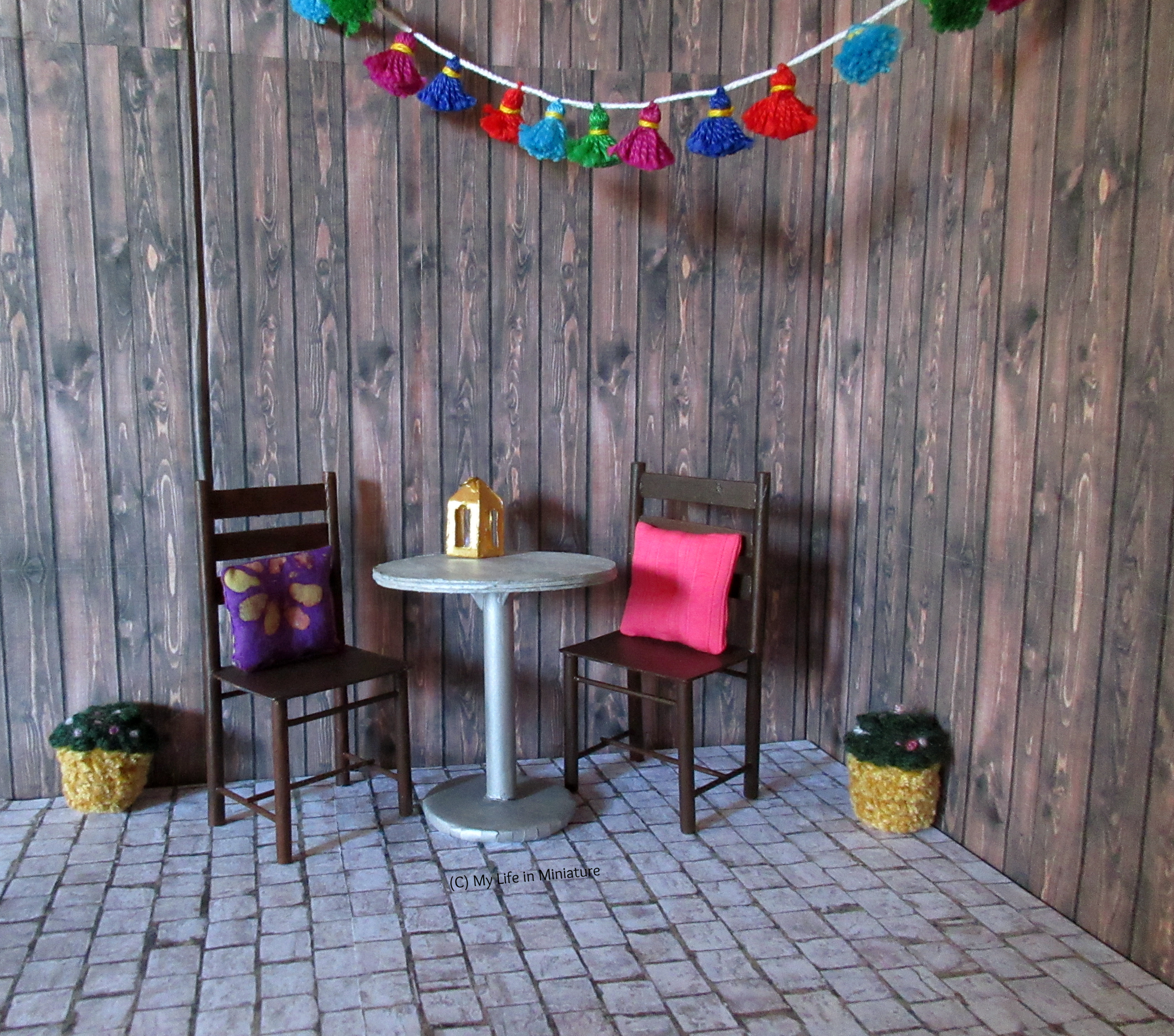 The courtyard outside Tea at Yaz's is pictured. It has dark wood walls and cobblestones, and is furnished with two brown chairs and a silver circular table. Two small flower pots are also on the floor, and a garland of multi-coloured tassels hangs across the top.