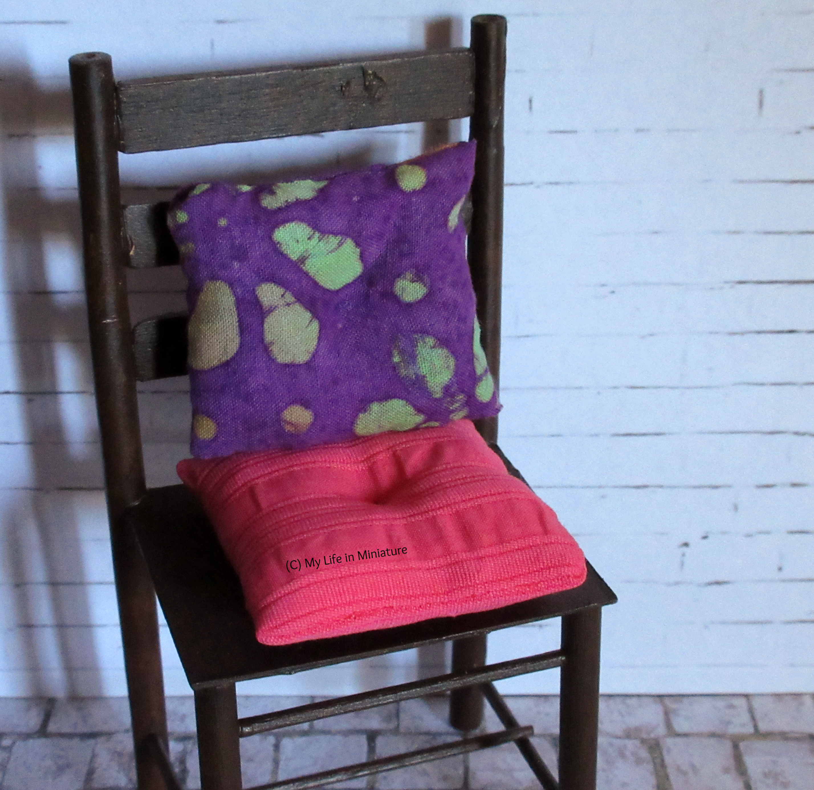 One of the brown chairs sits against a white brick background. On it are two cushions: one in purple batik fabric, one in pink fabric. Both have divots sewn in the centre.