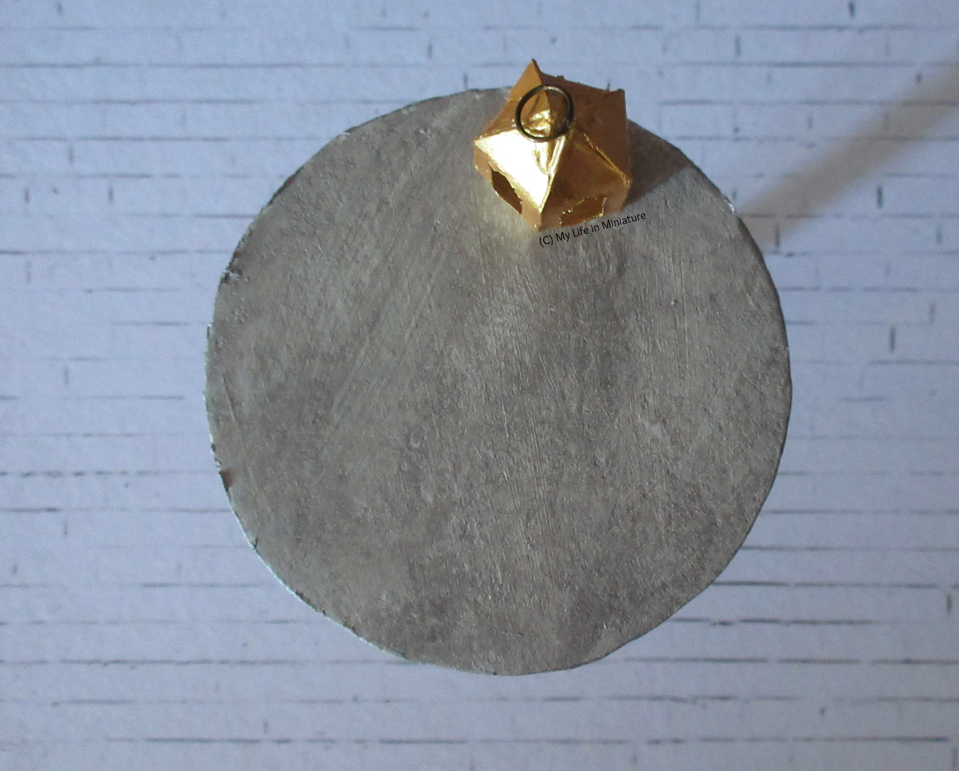 The silver table is photographed from above, over a white brick background. On it is the pentagonal gold lantern. The top is textured.