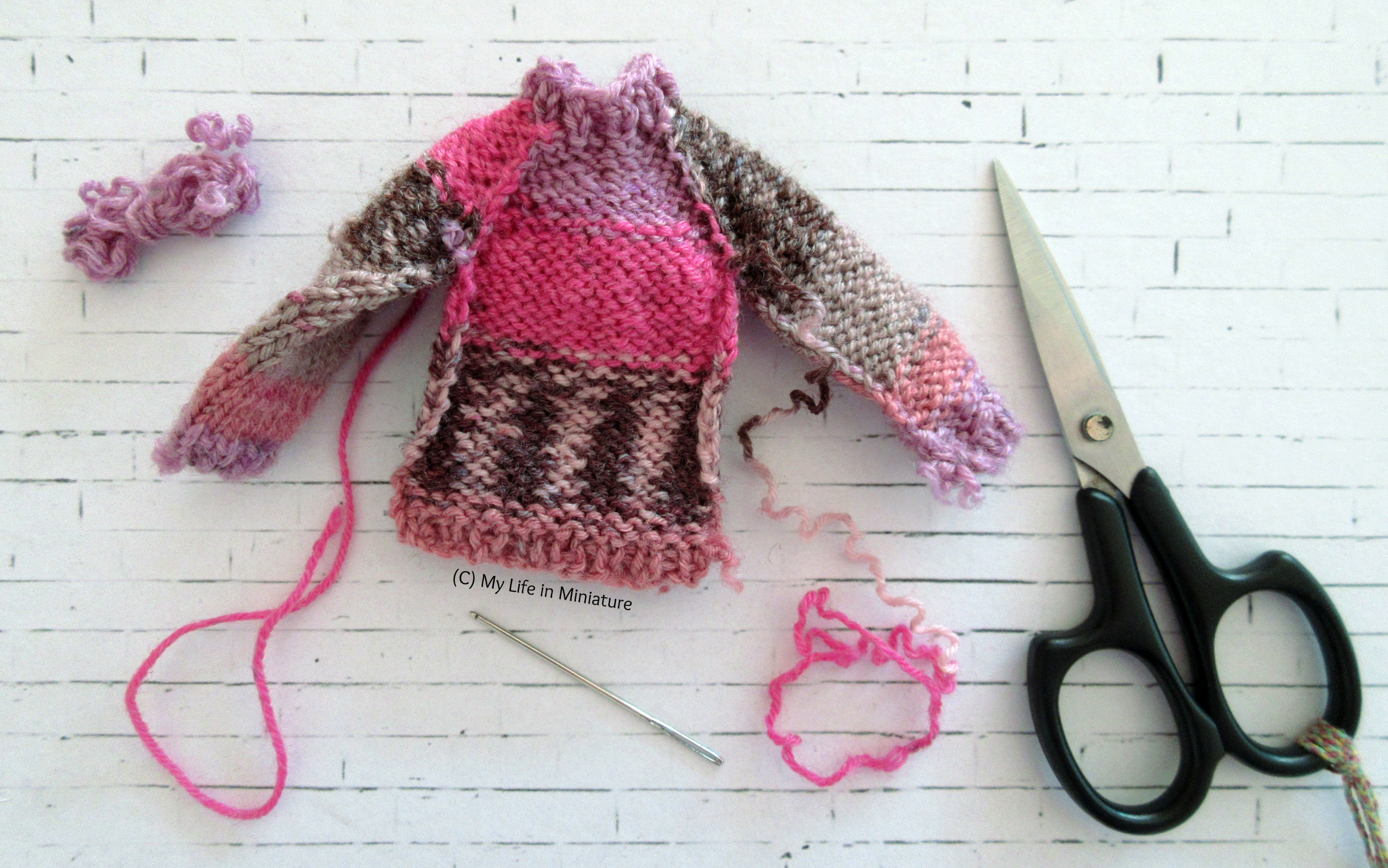 The pink jumper is shown mid-assembly on a white brick background. The four panels are sewn together, but the arm and side seams are not sewn yet. A needle and a pair of embroidery scissors are also visible.