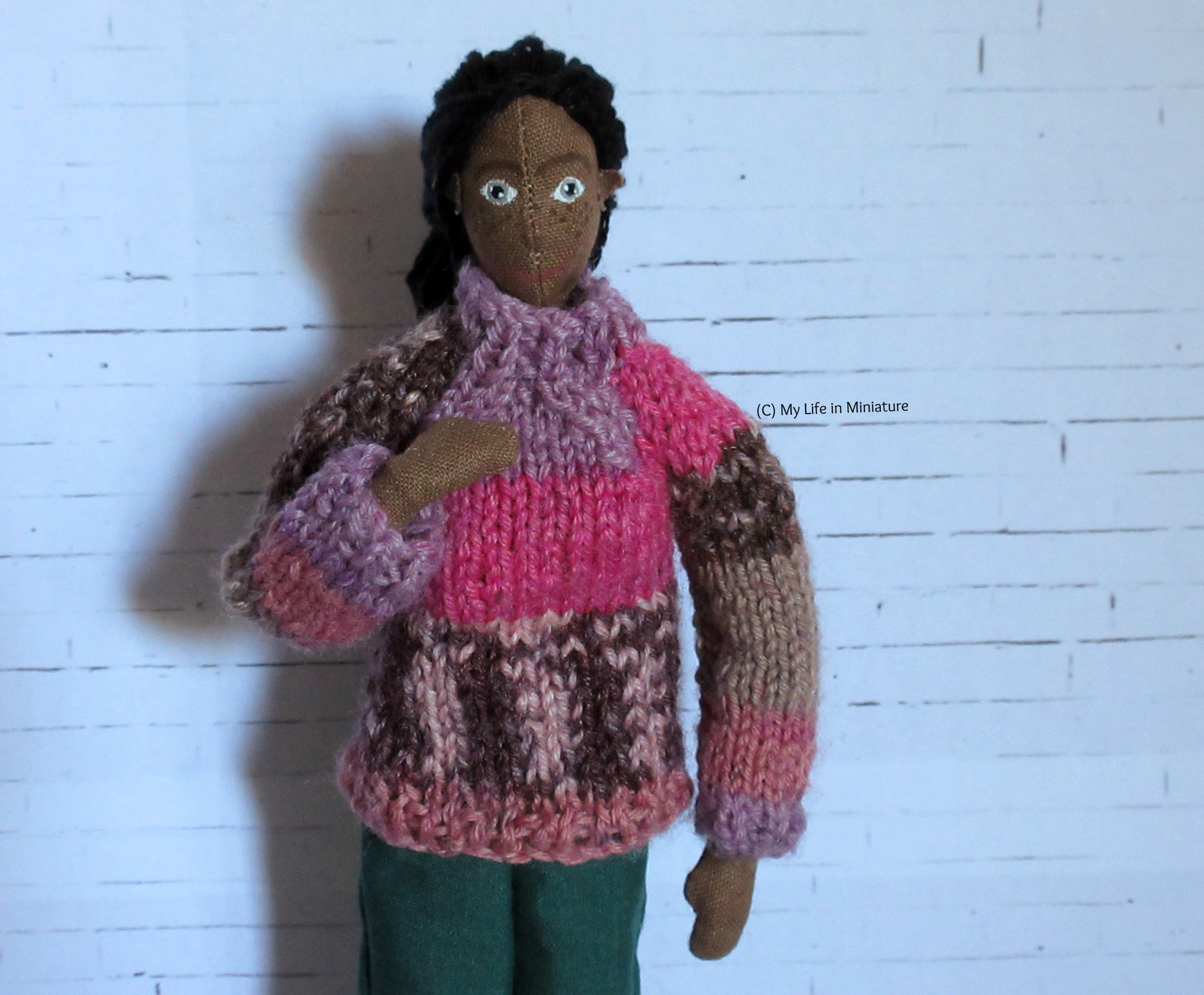 Petra wears the pink jumper, which now fits better at the neck, has longer sleeves, and a slimmer body. She looks at the camera.