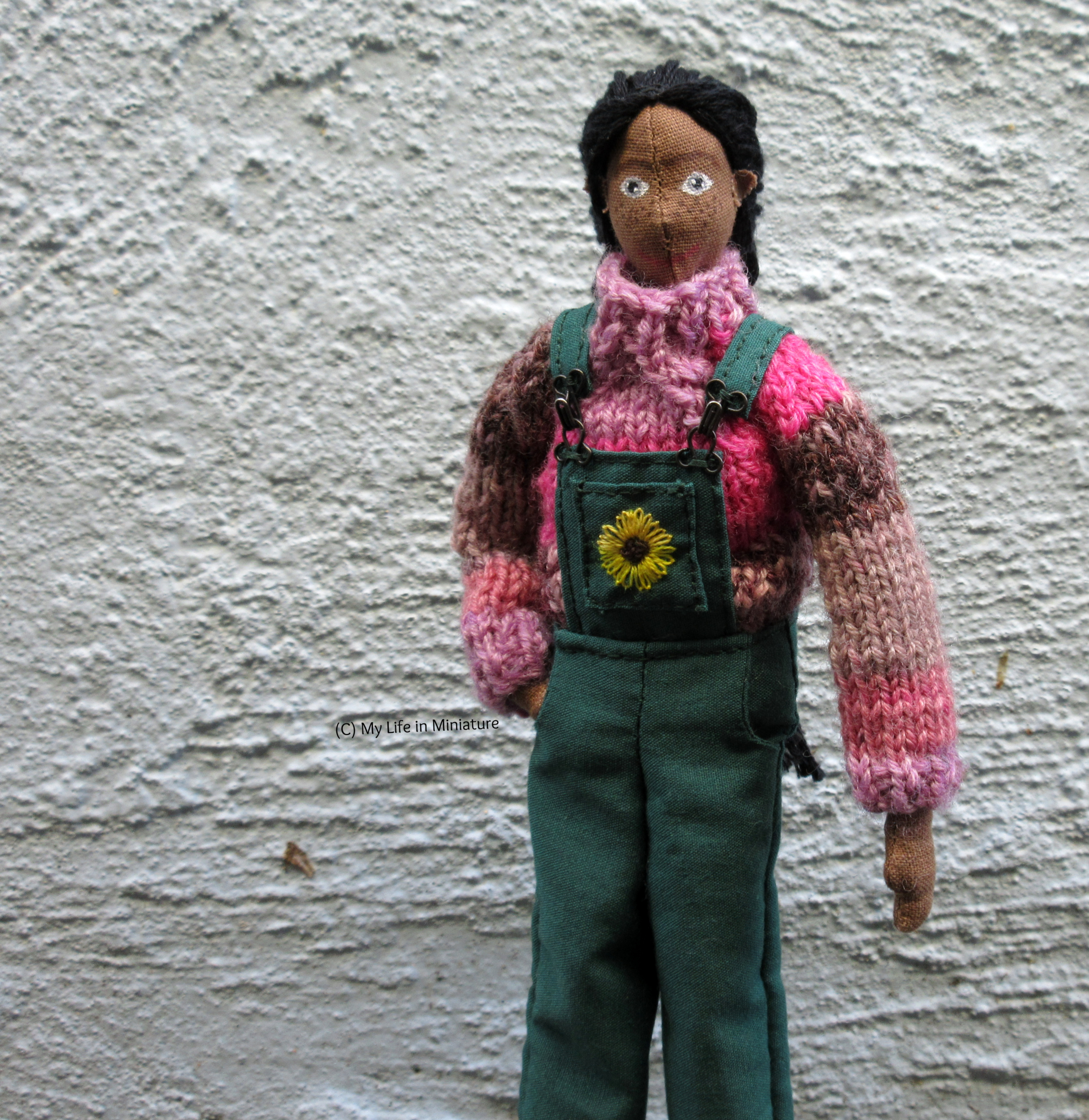 Petra wears the pink jumper under her green dungarees, one hand in her pocket. She's outside, against a pale blue textured wall, looking at the camera.